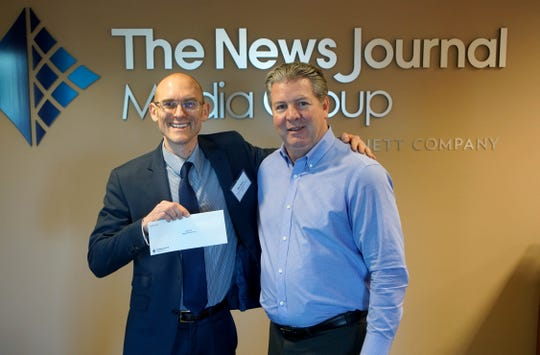 Wes Davis with West End Neighborhood House receives a check from News Journal publisher Tom Donovan.