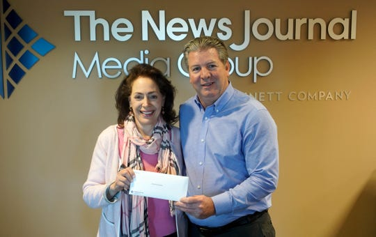Trish Fulvio with the Still Strong Foundation receives a check from News Journal publisher Tom Donovan.