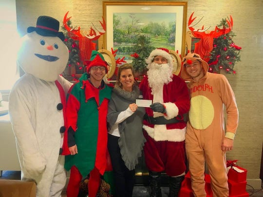 Motorcycle Santa, along with an elf and helpers, gives a check for $5,000 to Ronald McDonald House of Delaware Development Director Barbara Loeslein last year.