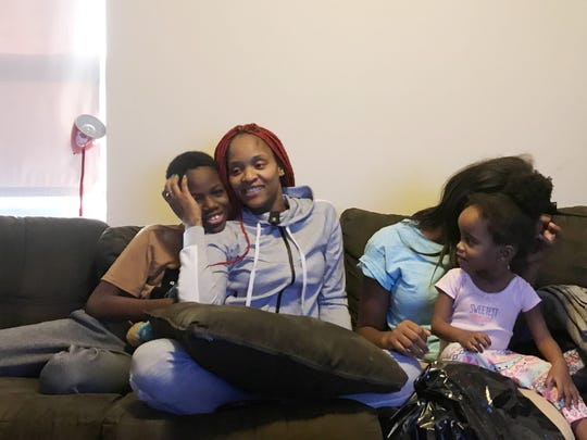 Dominique Green holds her 11-year-old son, Kewann Young Jr, as she sits beside her eldest, 13-year-old Acoyonna Miles-Mason and her 2-year-old Dawnay Mason.