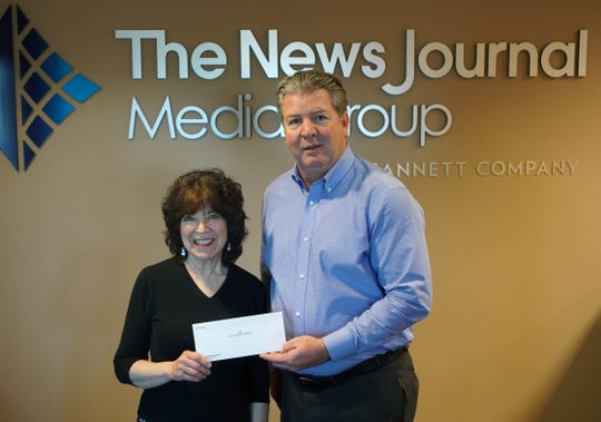 Barbara Palladino with SOAR Survivors of Abuse in Recovery receives a check from News Journal publisher Tom Donovan.