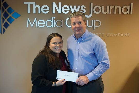 Lynn Biddle-Cloud with Delaware Guidance Services for Children and Youth, Inc. receives a check from News Journal publisher Tom Donovan.