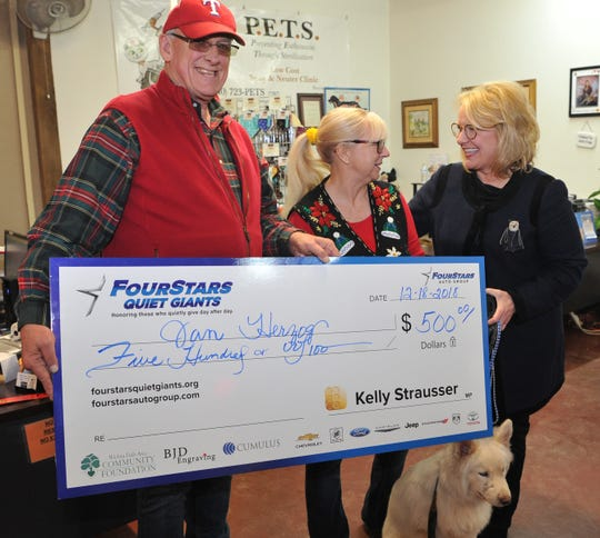 Radio broadcaster Jim Russell presents P.E.T.S volunteer Jan Herzog with a award after she received a $500 check from Four Stars Quiet Giants for the Underdog Express, a program she championed that helps transport to New York sheltered dogs who might otherwise be euthanized. .