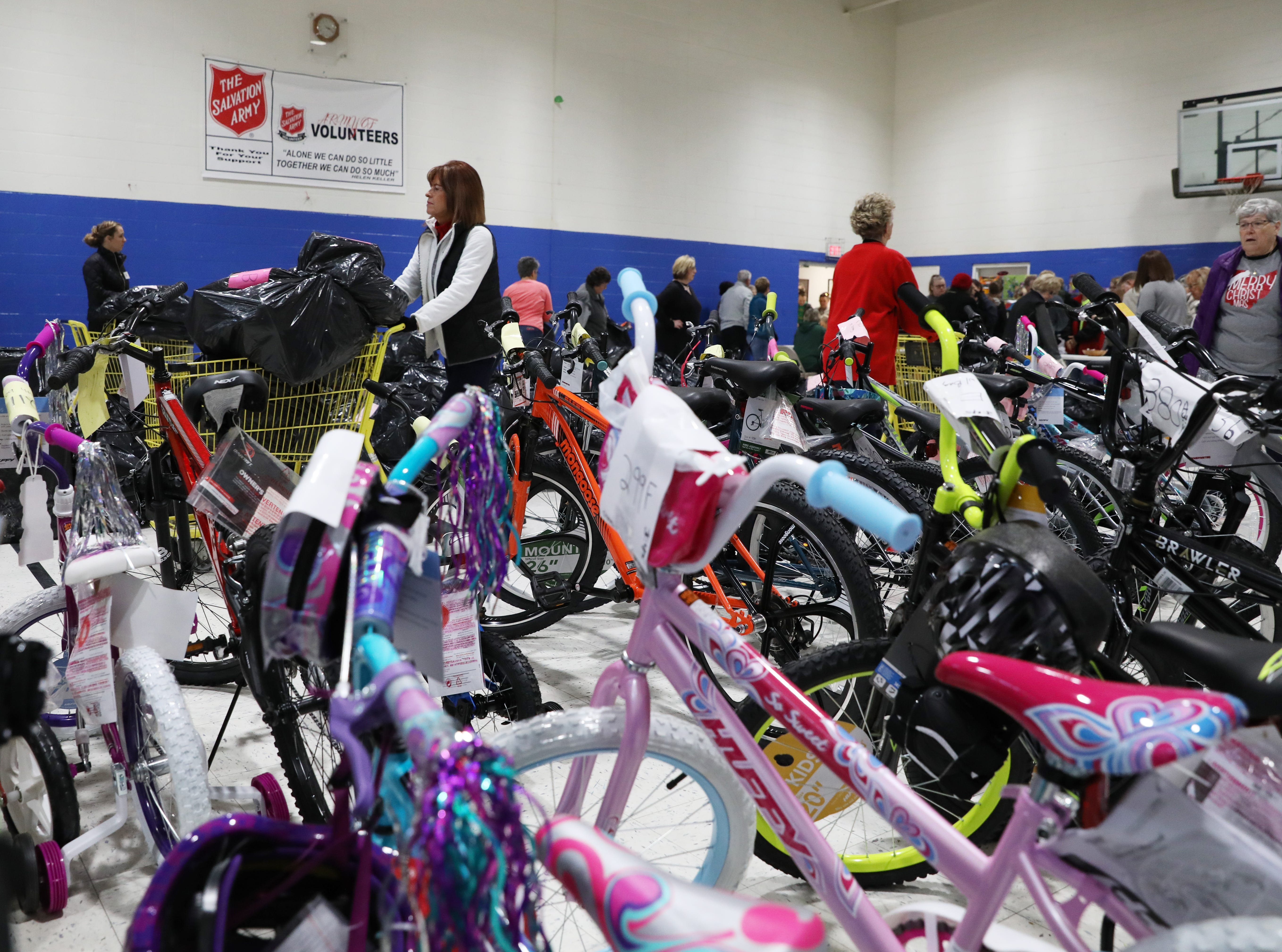 Volunteers place bags of presents during the Salvation Army present and food disbursement day on Tuesday.