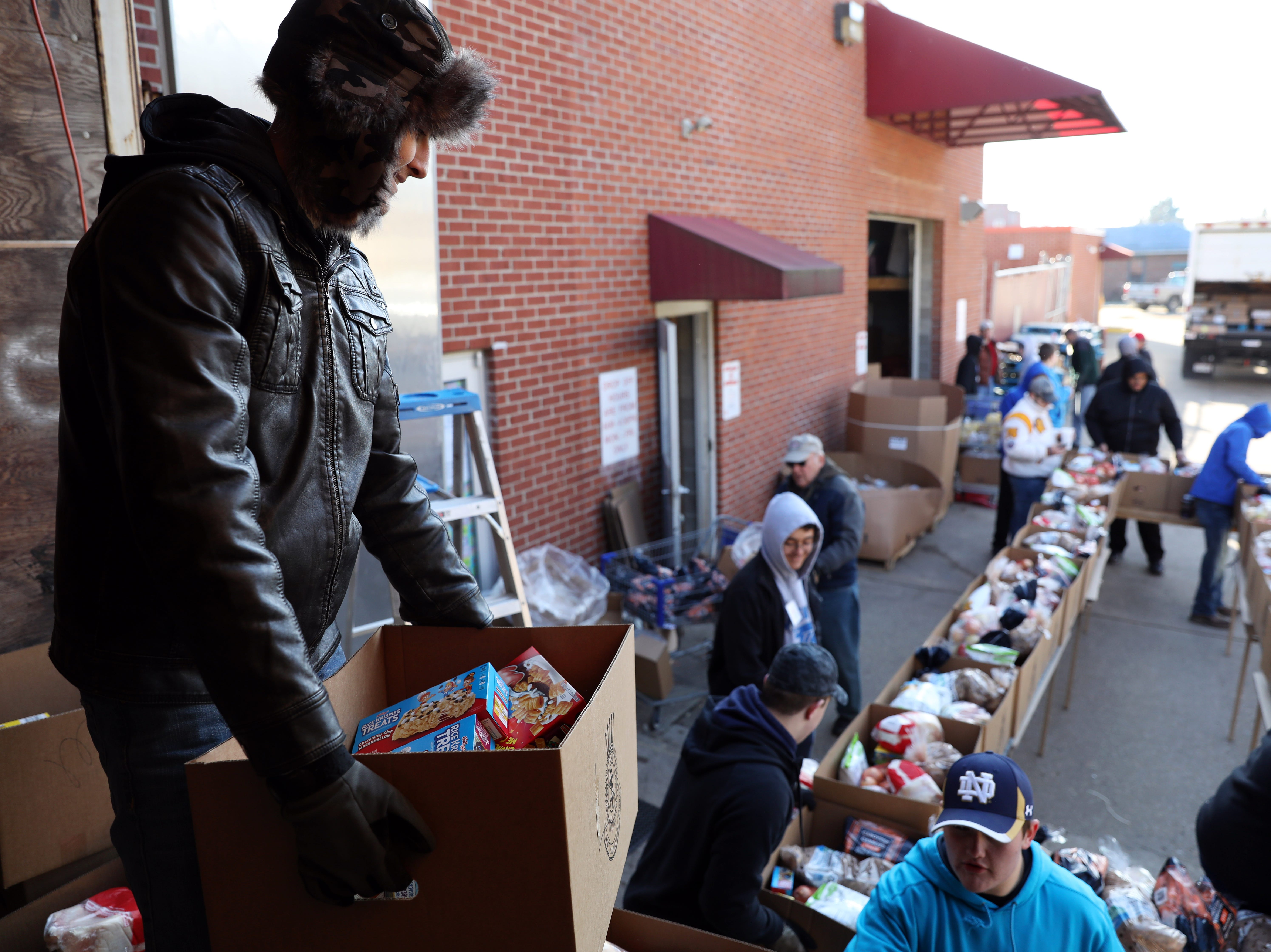 Brodee Creeks holds a box of food while volunteering at the Salvation Army on Tuesday.