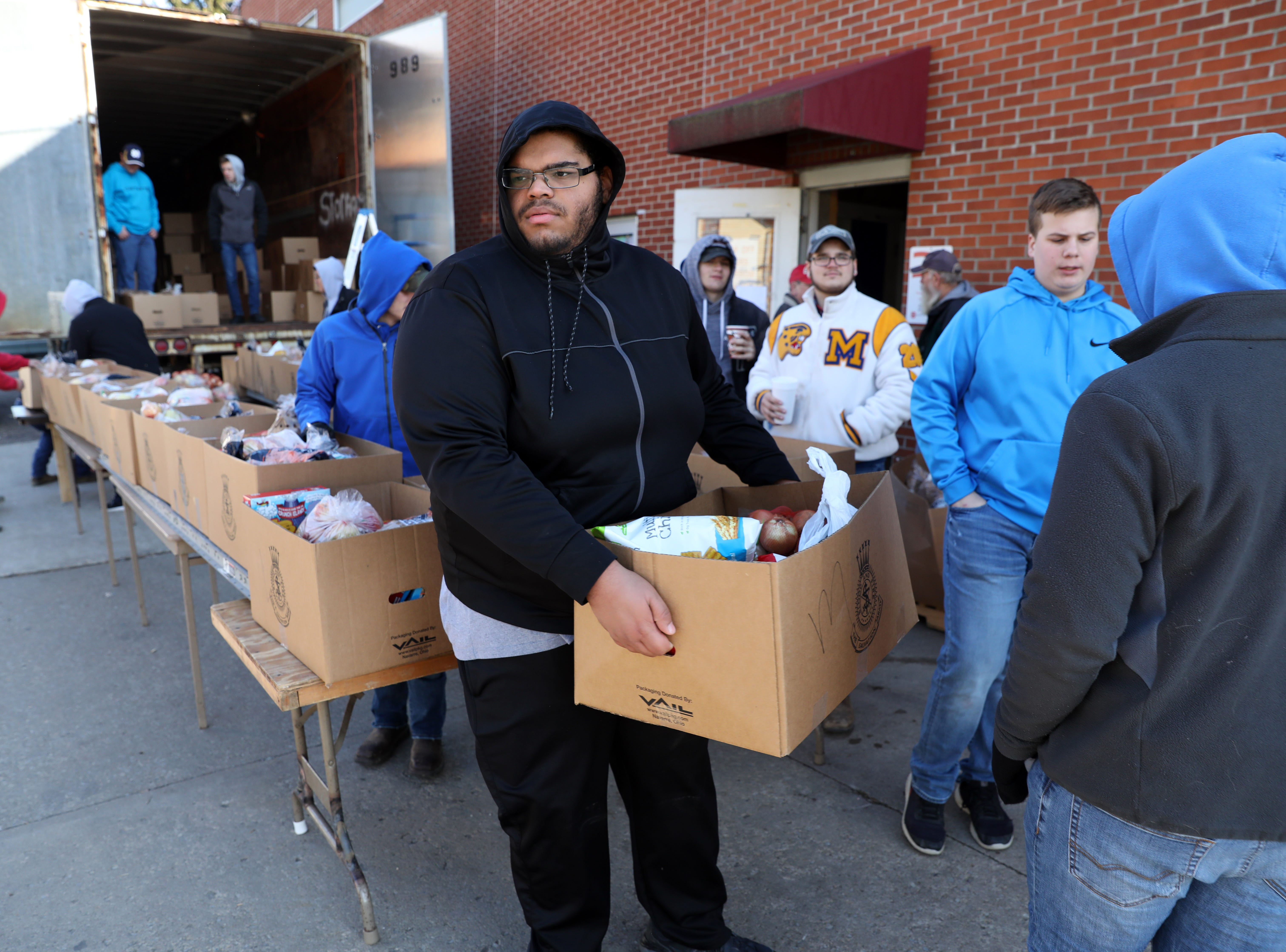 Maysville High School football player Jakob Plummer carries a box of food while volunteer at the Salvation Army on Tuesday.