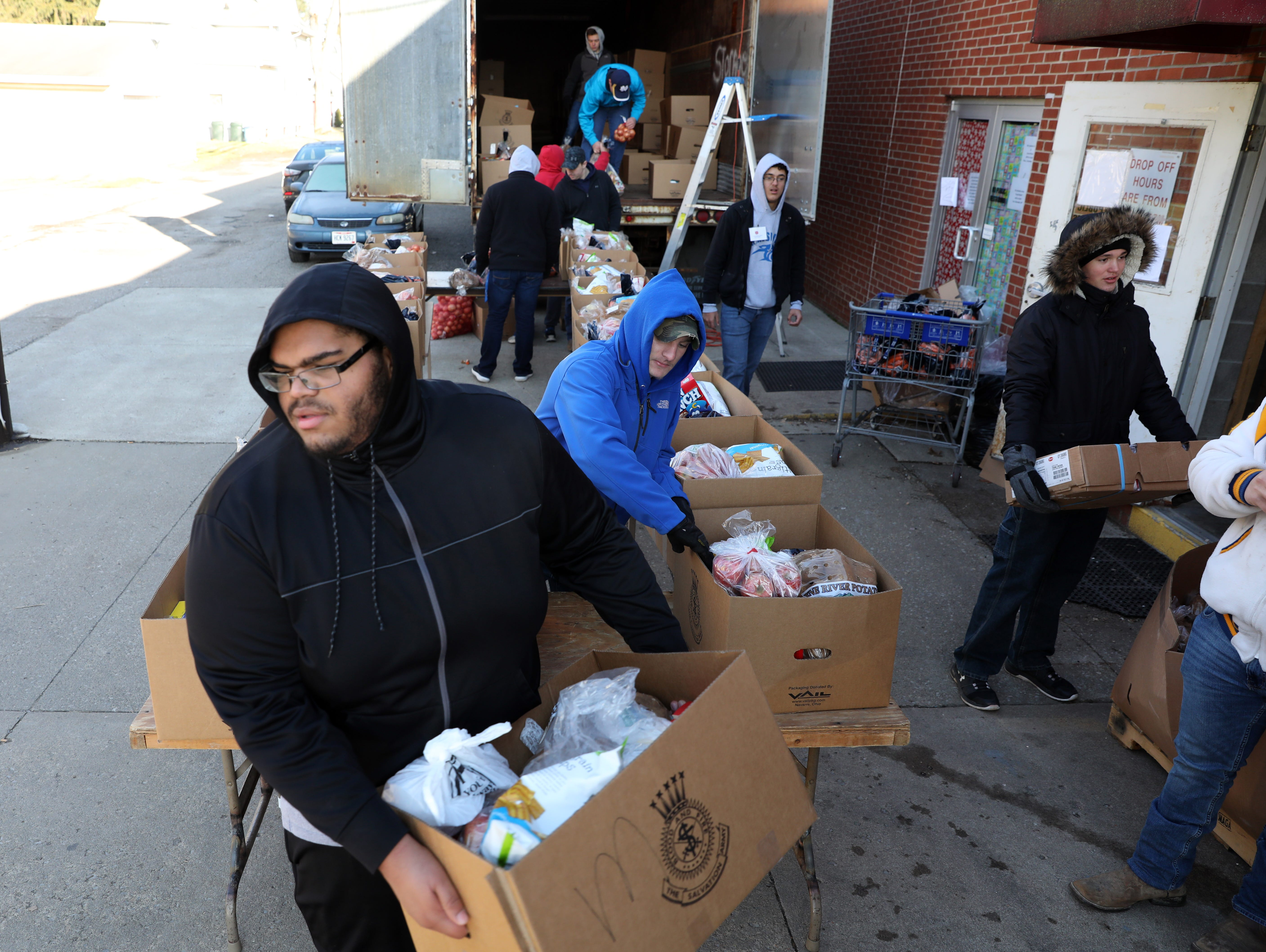 Maysville High School football player Jakob Plummer carries a box of food while volunteering at the Salvation Army on Tuesday.