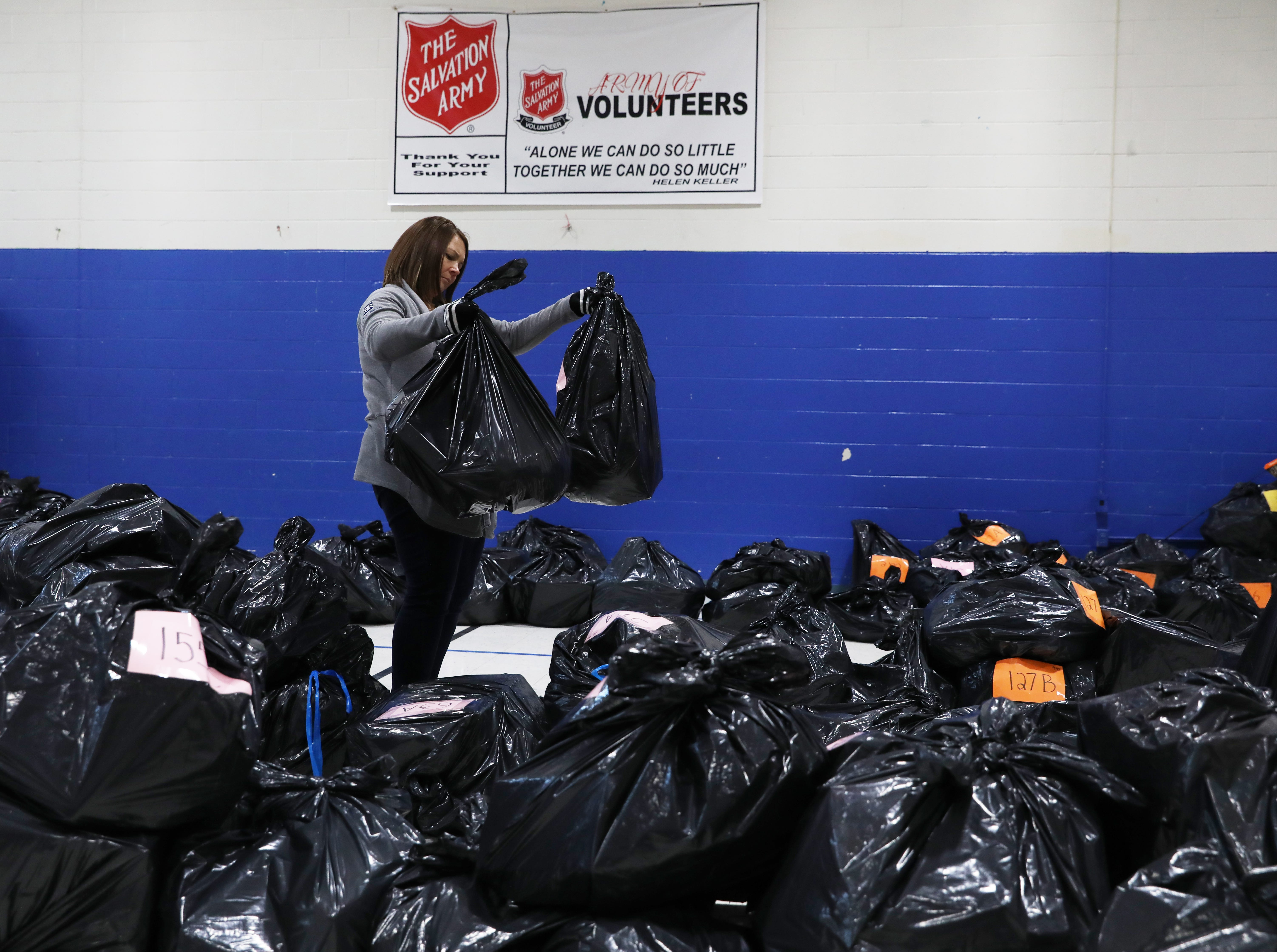 Volunteer Trisha McKenzie of Rankin and Rankin Insurance checks bags during the Salvation Army present and food disbursement day on Tuesday.