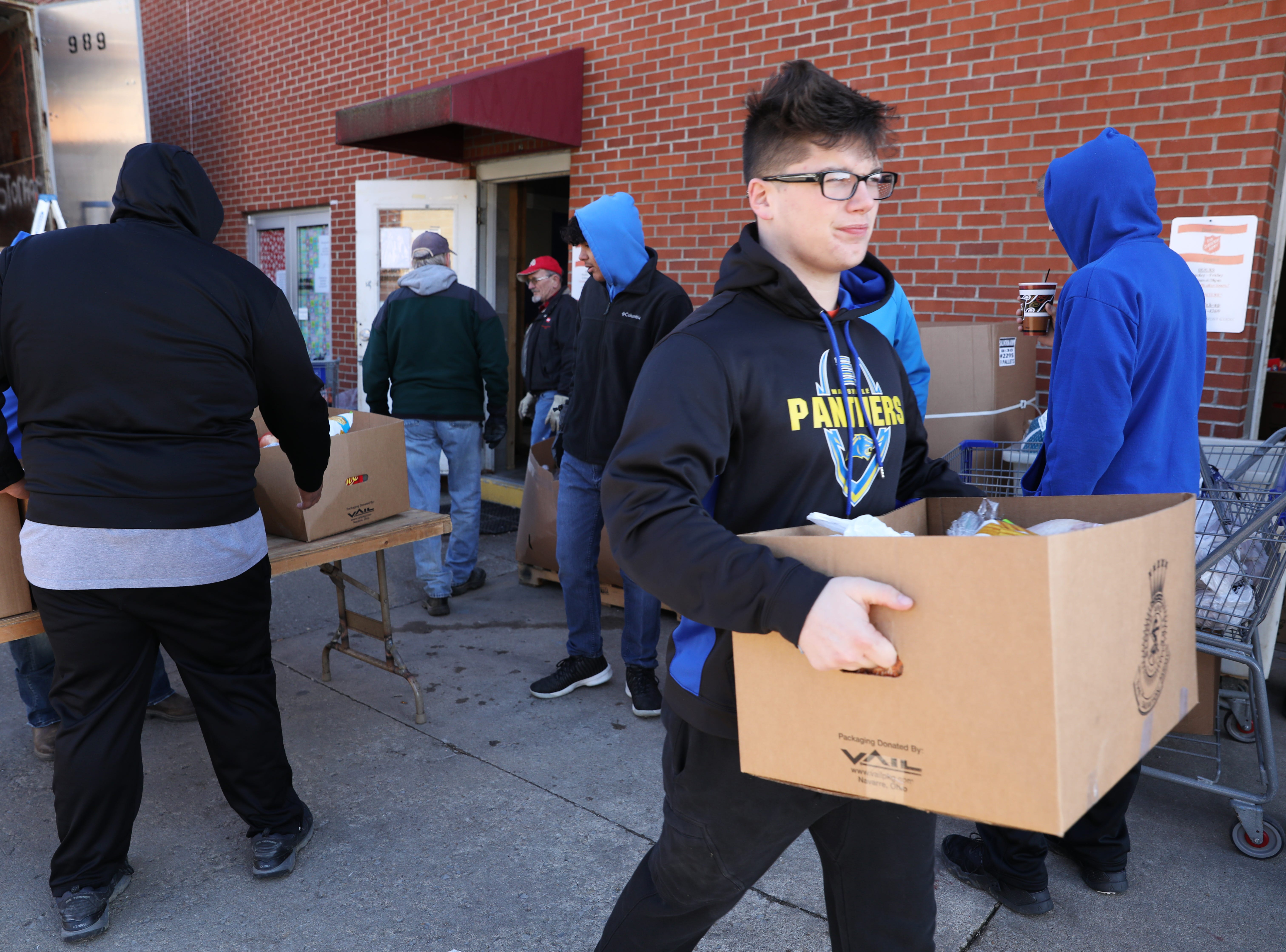 Maysville High School football player Easton Smith carries a box of food while volunteering at the Salvation Army on Tuesday.