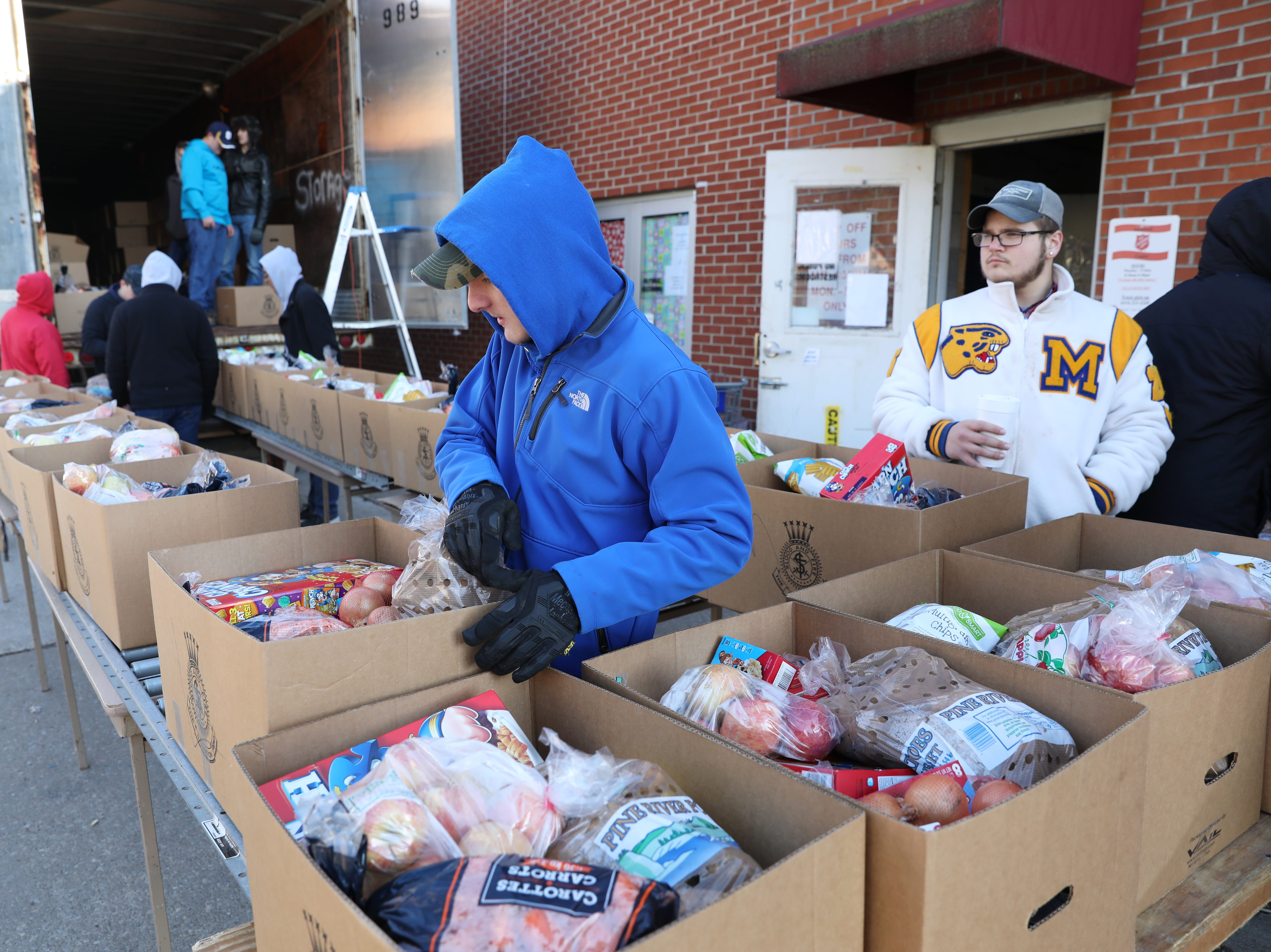 Maysville High School football player Kayon Zinn moves boxes of food while volunteering at the Salvation Army on Tuesday.