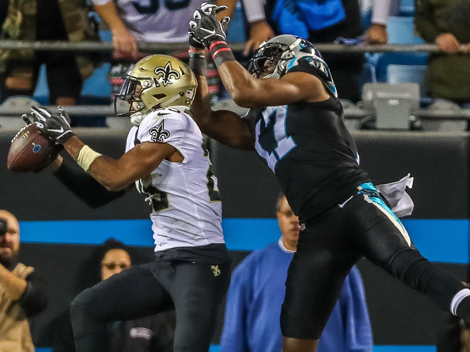 New Orleans Saints cornerback Eli Apple intercepts a ball in the end zone in front of Carolina Panthers wide receiver Devin Funchess during the second quarter at Bank of America Stadium.