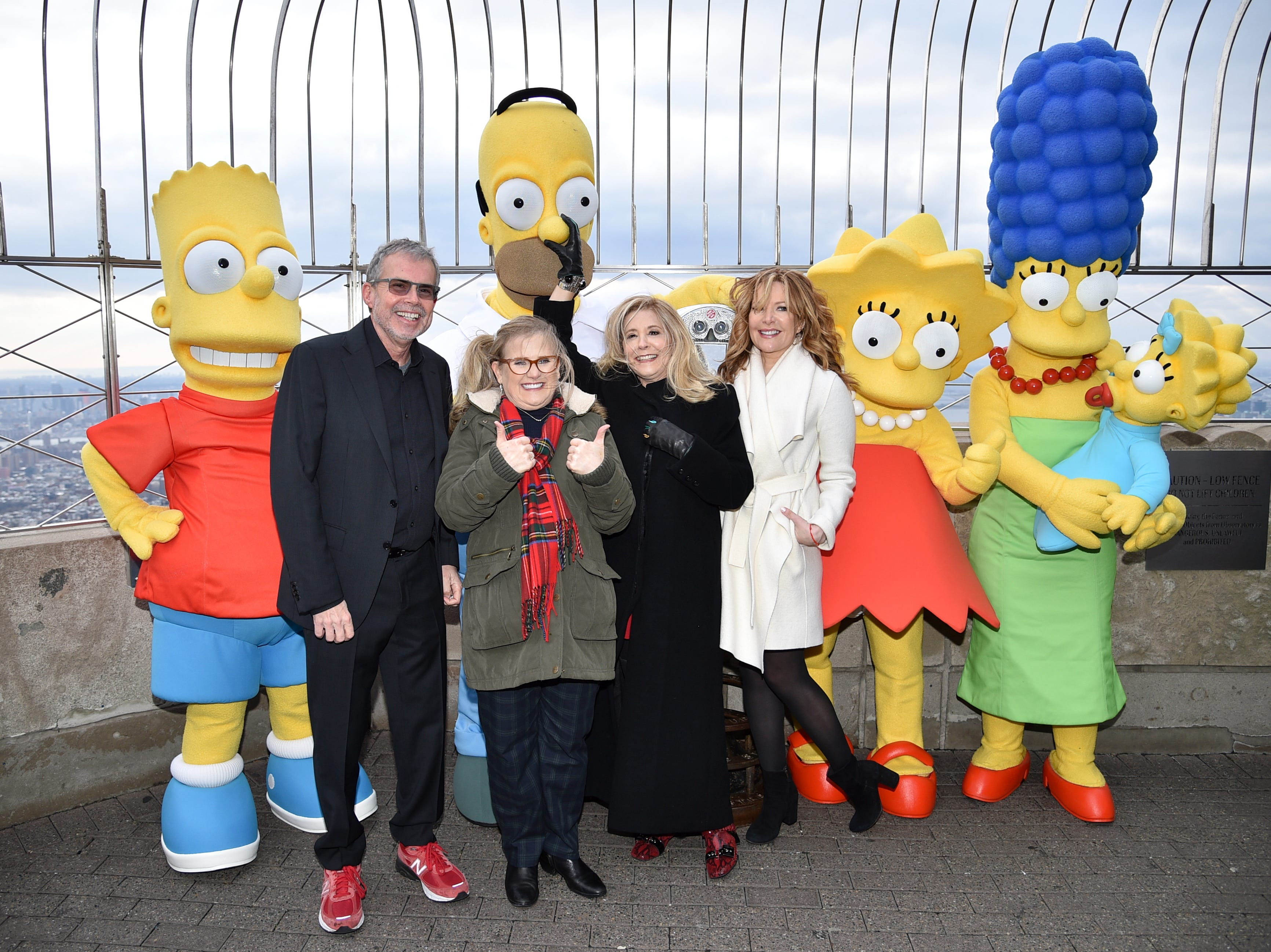 """Producer Mike Scully, left, voice actor Nancy Cartwright, voice actor Pamela Hayden and writer Stephanie Gillis pose with """"The Simpsons"""" costumed characters during Fox's """"The Simpsons"""" 30th anniversary celebration at the Empire State Building on Monday, Dec. 17, 2018, in New York. (Photo by Evan Agostini/Invision/AP) ORG XMIT: NYEA116"""