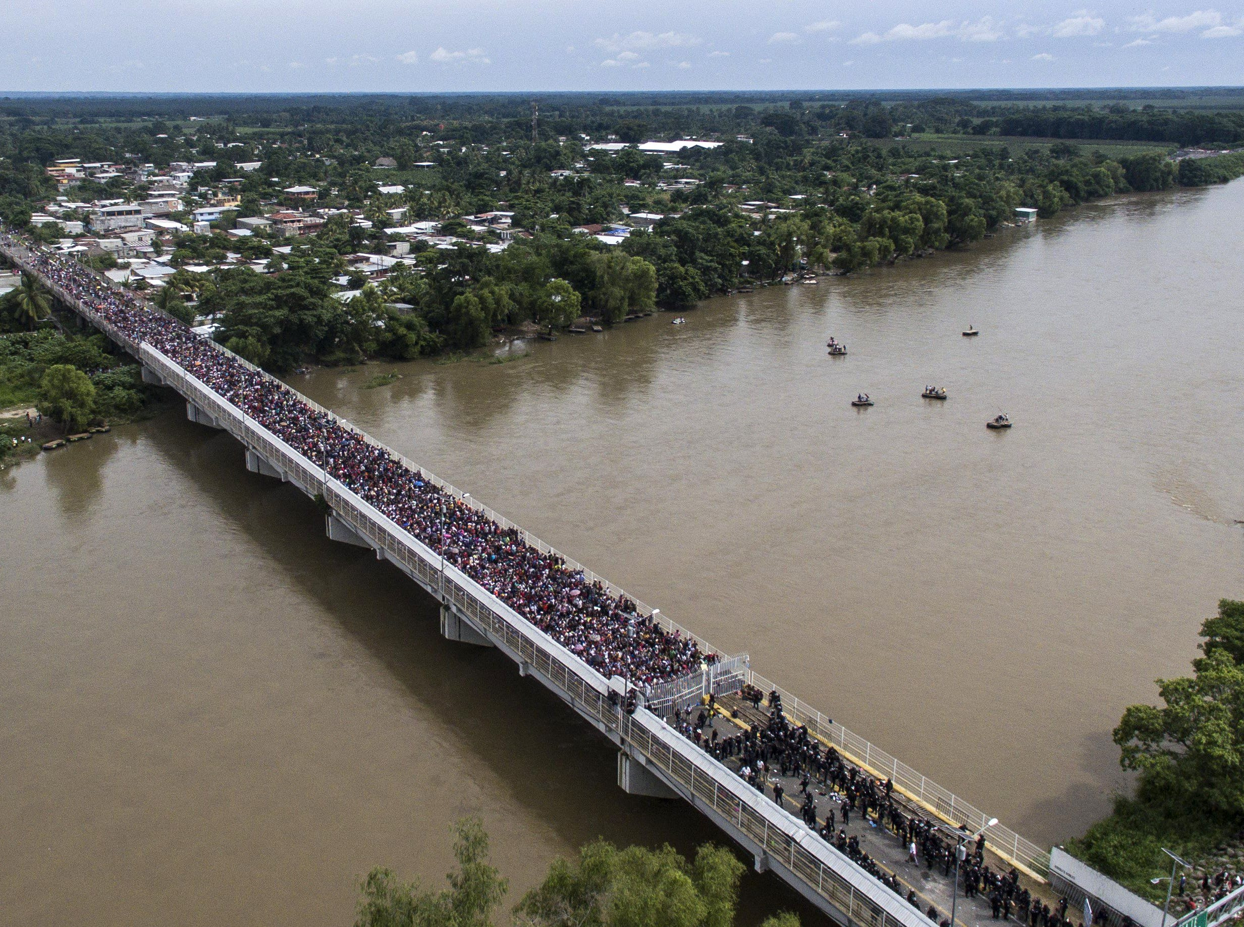 Aerial view of a Honduran migrant caravan heading to the US, as it is stopped at a border barrier on the Guatemala-Mexico international bridge in Ciudad Hidalgo, Mexico, on Oct. 19, 2018.  Honduran migrants who have made their way through Central America were gathering at Guatemala's northern border with Mexico, despite President Donald Trump's threat to deploy the military to stop them entering the United States.