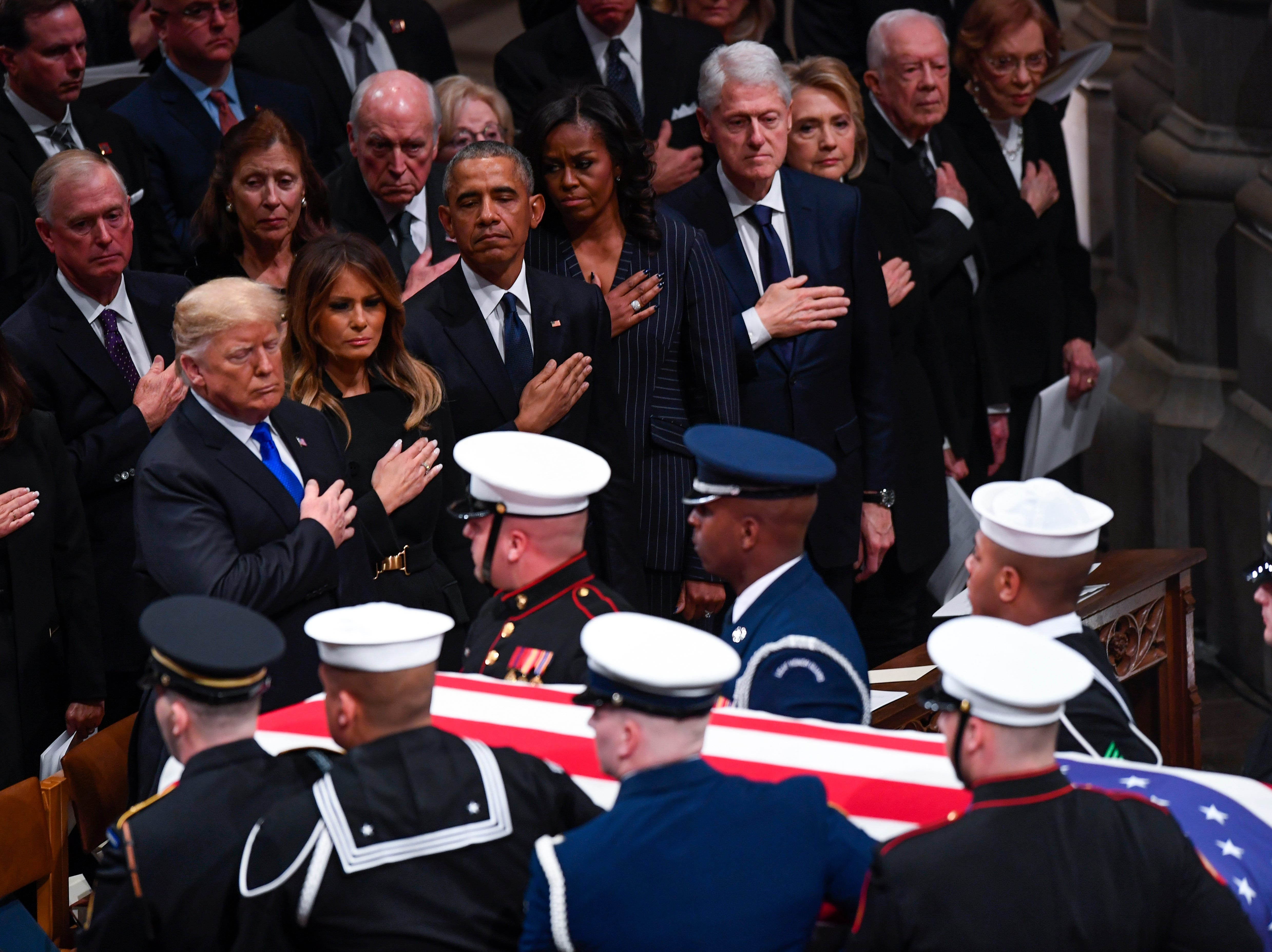 President Donald Trump and First Lady Melania Trump with former President Barack Obama and Michelle Obama, former President Bill Clinton and former Secretary of State Hillary Clinton, and former President Jimmy Carter and Rosalynn Carter place hands on heart at conclusion of the state funeral for former President George H.W. Bush at the Washington National Cathedral on Dec. 5, 2018.