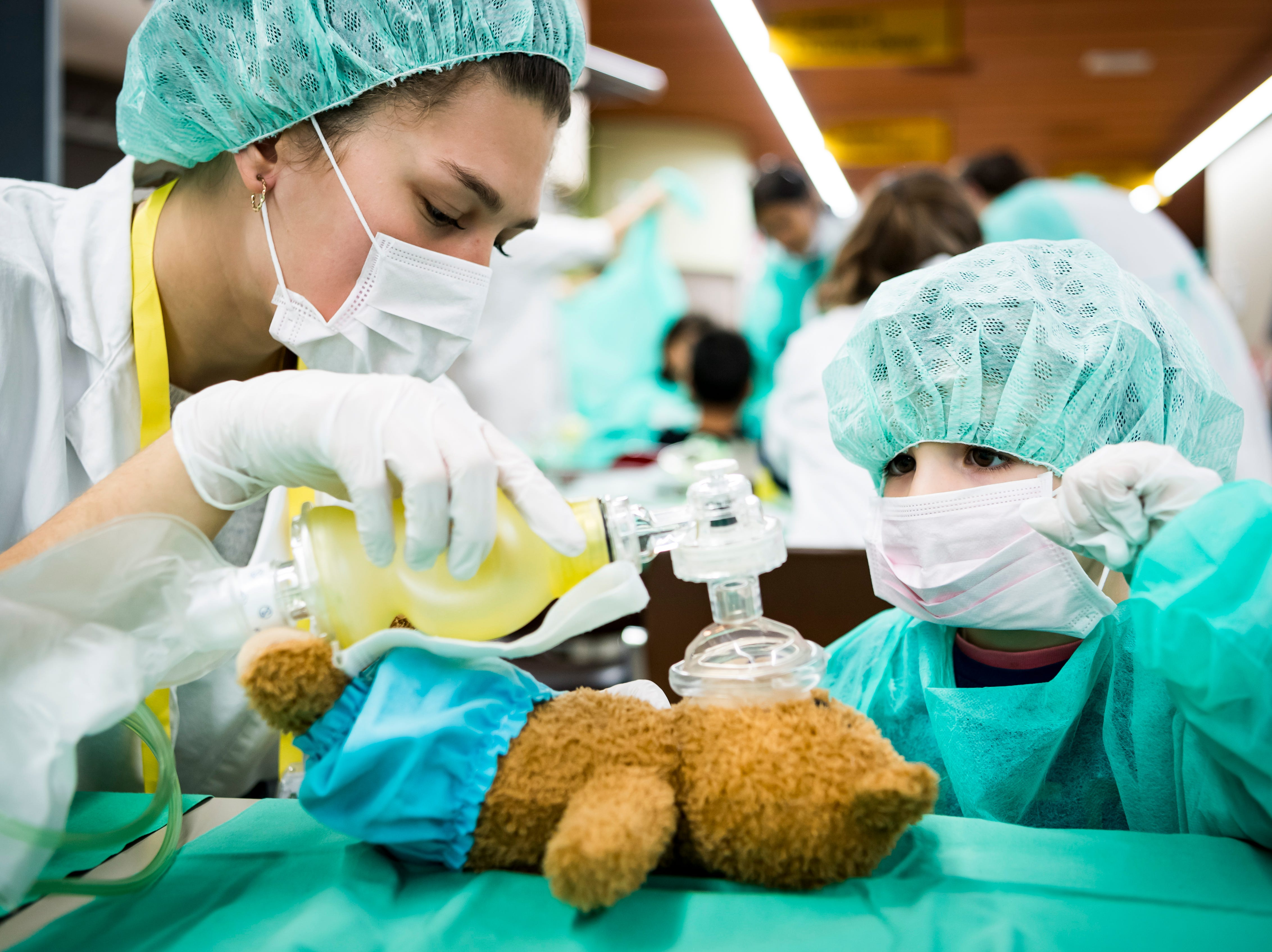 """A child cares for a teddy bear with the help of a medical student at the 11th edition of the """"Teddy Bear Hospital"""" at the CHUV hospital in Lausanne, Switzerland on Nov. 18, 2018. Teddy Bear Hospital (TBH) is an international project, whose aim is to reduce childhood anxiety about medical environments, procedures and professionals."""