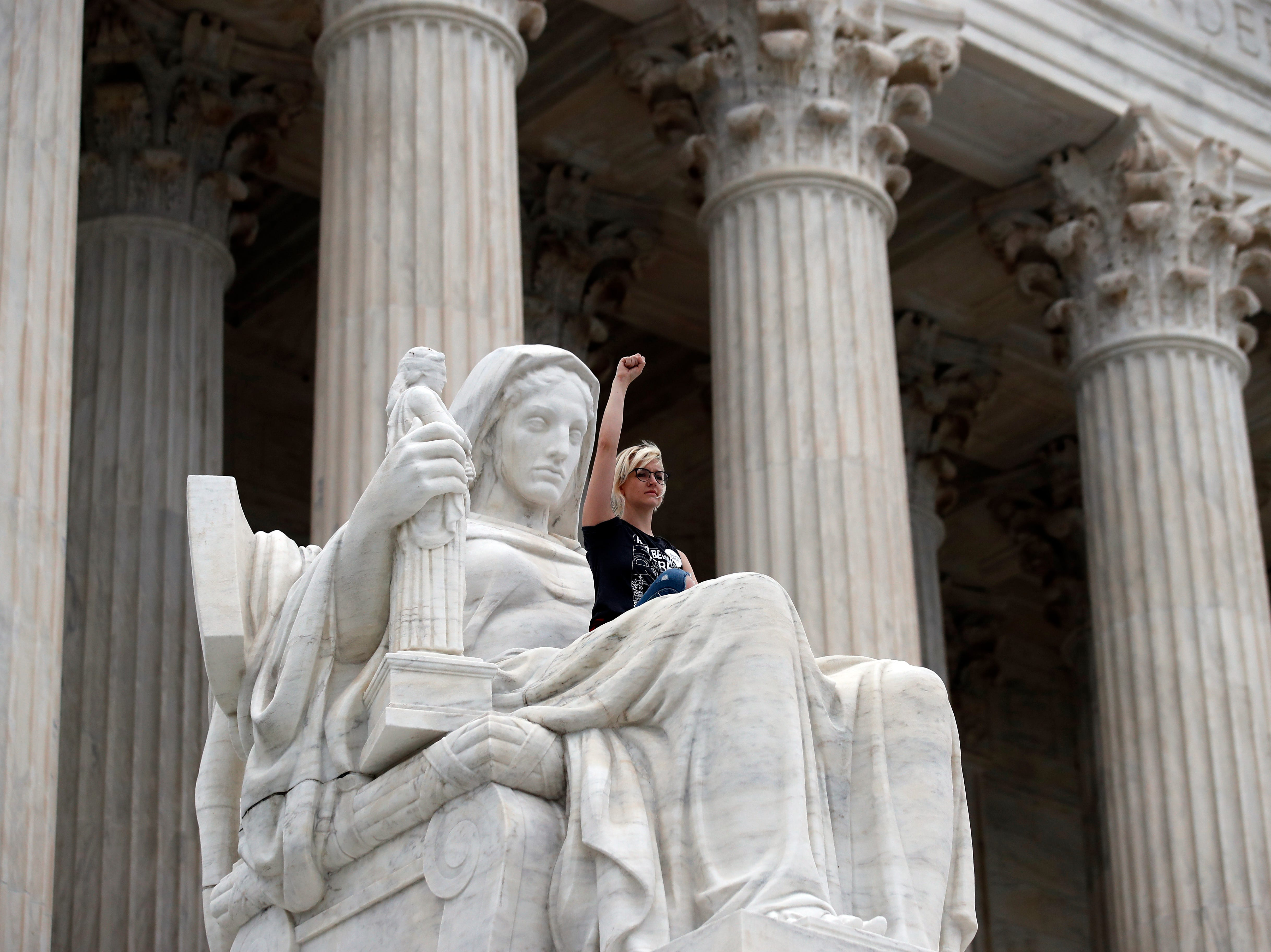 Jessica Campbell-Swanson, from Denver, sits in the lap of the Contemplation of Justice statue as activists protest on the steps of the Supreme Court after the confirmation vote of Supreme Court nominee Brett Kavanaugh, on Capitol Hill, Oct. 6, 2018 in Washington.