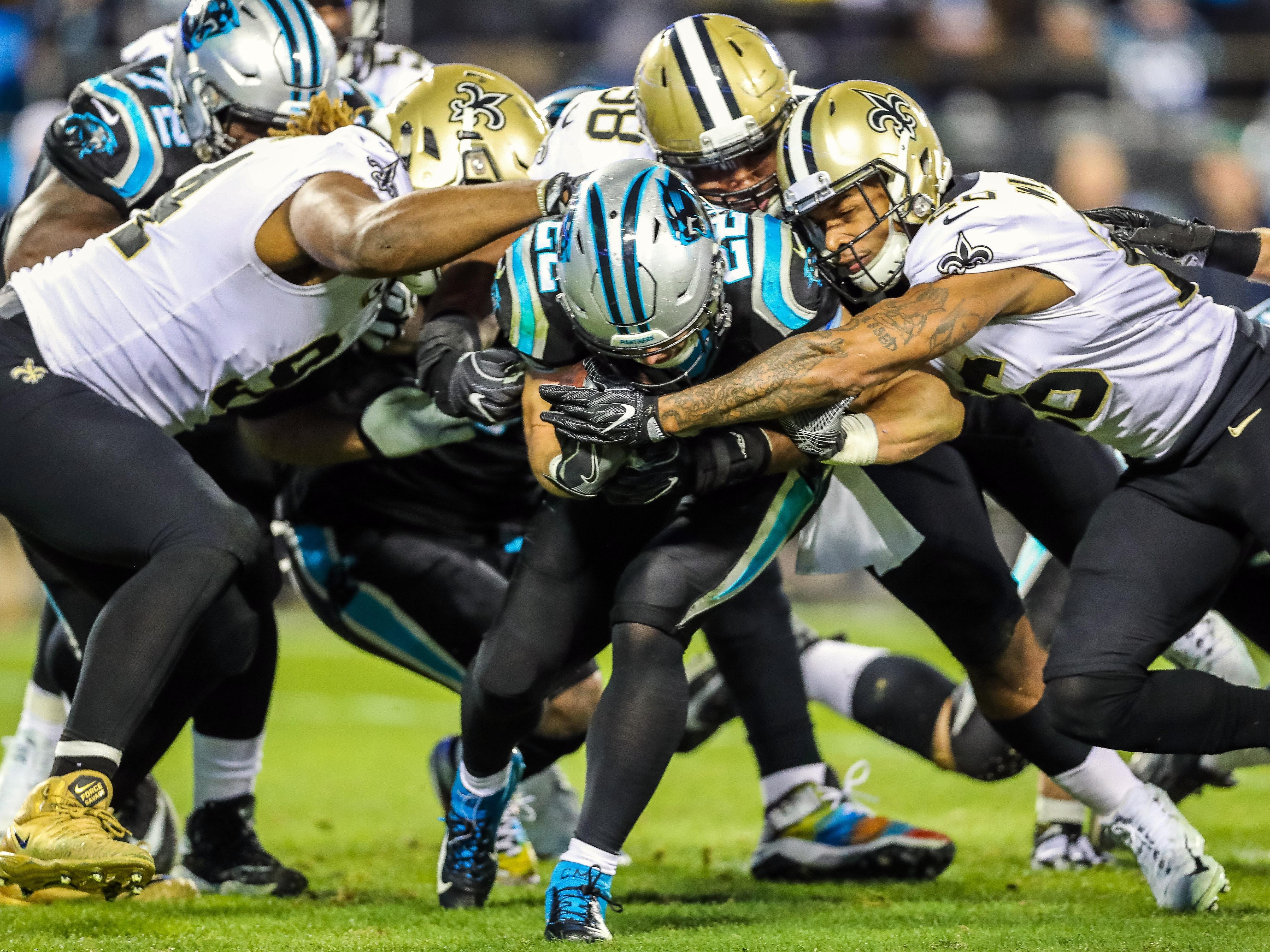 Carolina Panthers running back Christian McCaffrey is wrapped up by the New Orleans Saints defense during the second quarter at Bank of America Stadium.