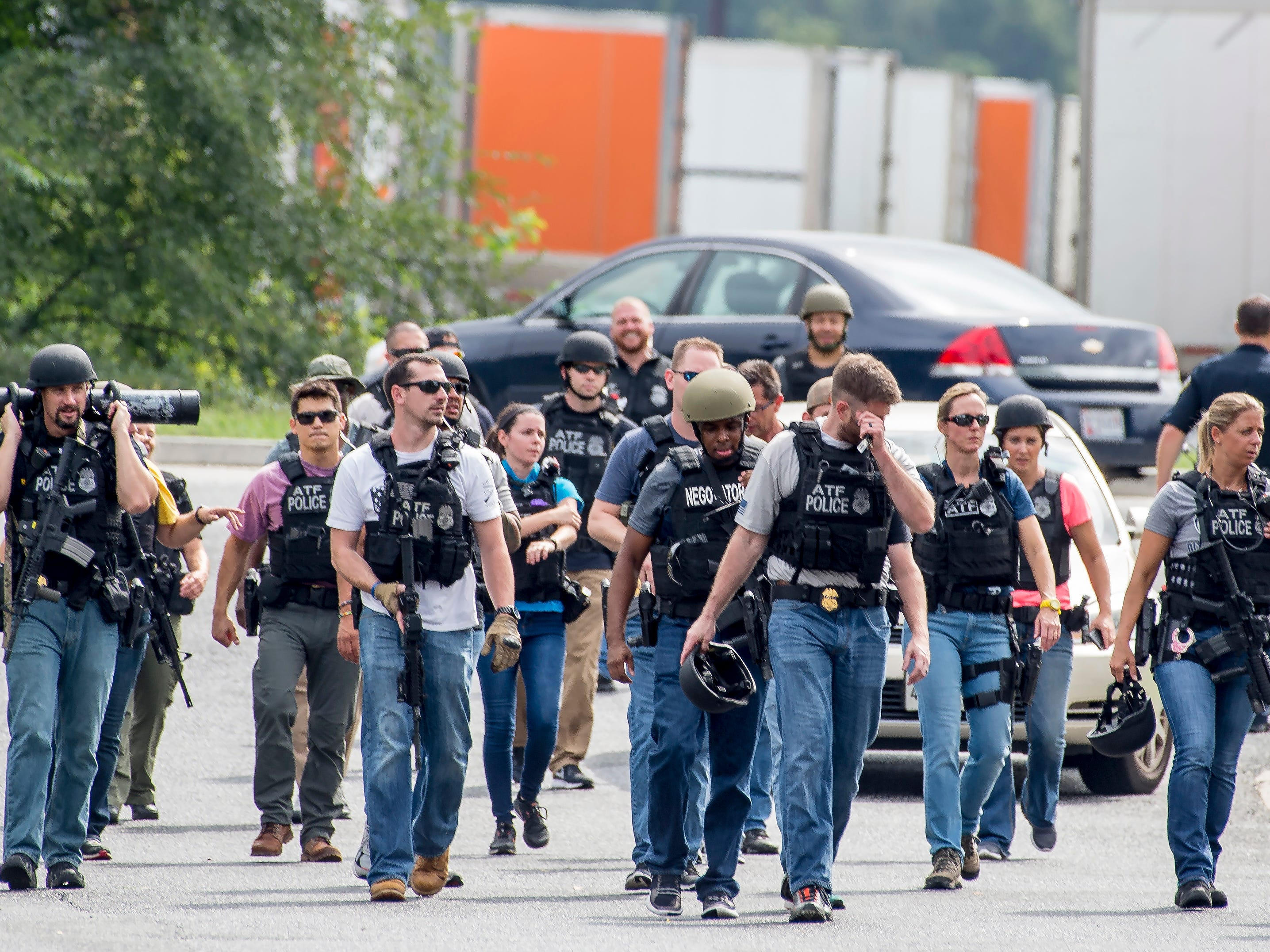 Numerous Bureau of Alcohol, Tobacco, Firearms and Explosives (ATF) agents on patrol after clearning an area near a warehouse as police search for a gunman who fled the scene of a shooting at a Rite Aid Distribution Center in Aberdeen, Md, Sept, 20, 2018. Media reports indicate numerous casualties in the shooting.