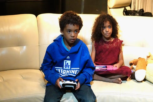 Christoper and Gabrielle look on at video games on the big screen TV.