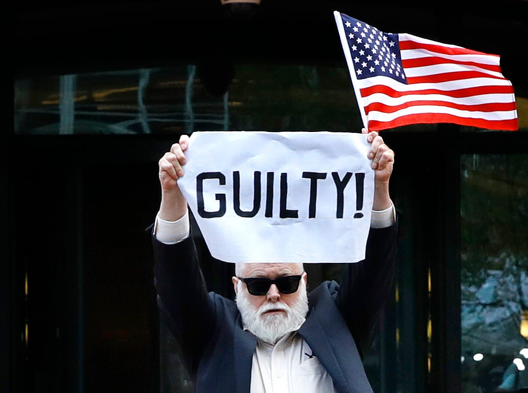 """Aug. 21, 2018: Protester Bill Christeson holds up a sign saying """"guilty"""" as the first count of guilty comes in at the trial of former Donald Trump campaign chairman Paul Manafort at a federal court in Alexandria, Va."""