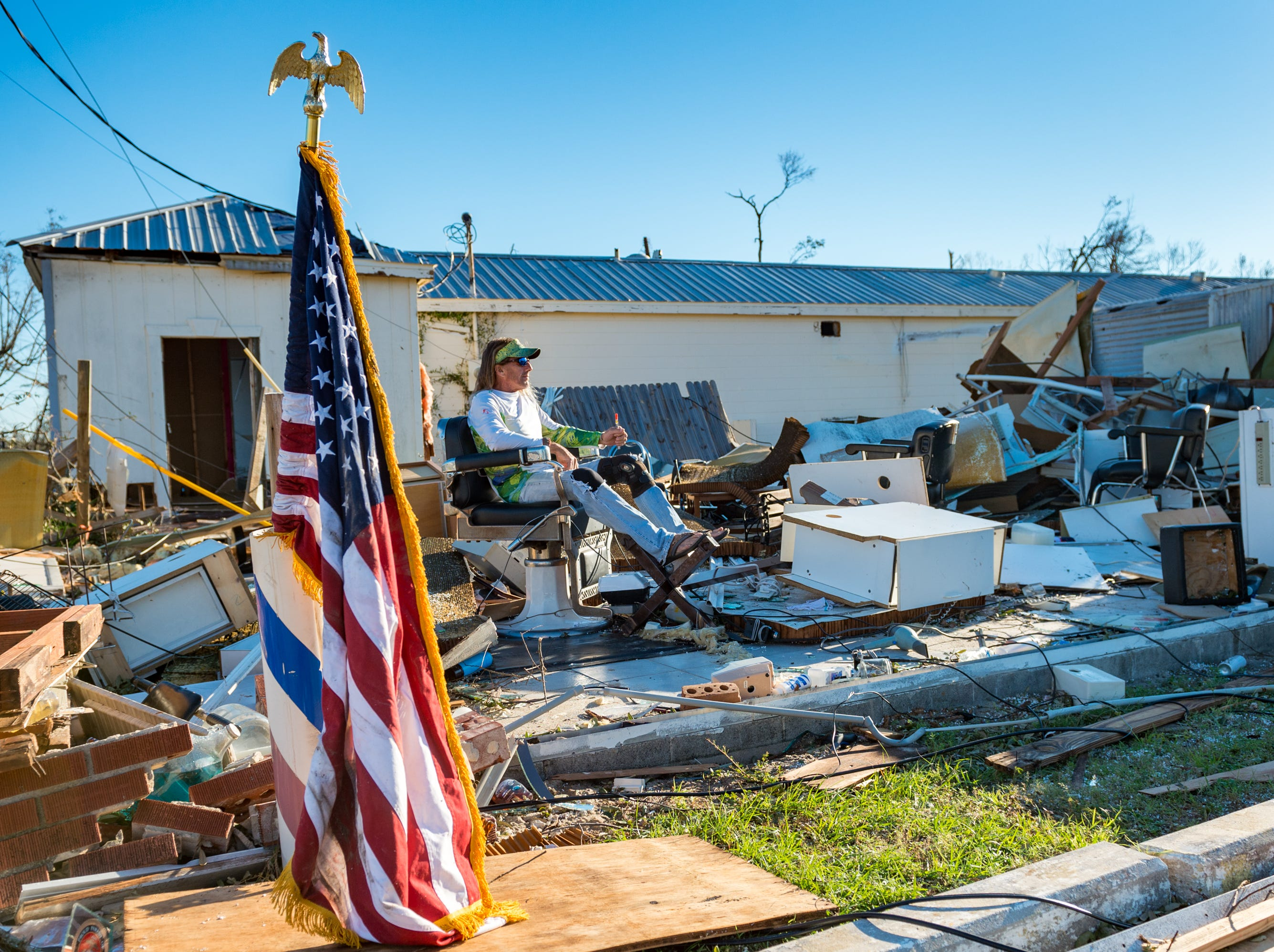 William Gay takes a break while helping a friend to find personal belongings in a barber shop on Highway 98 on Oct. 12, 2018 in Panama City, Fla. after Hurricane Michael caused widespread damage.
