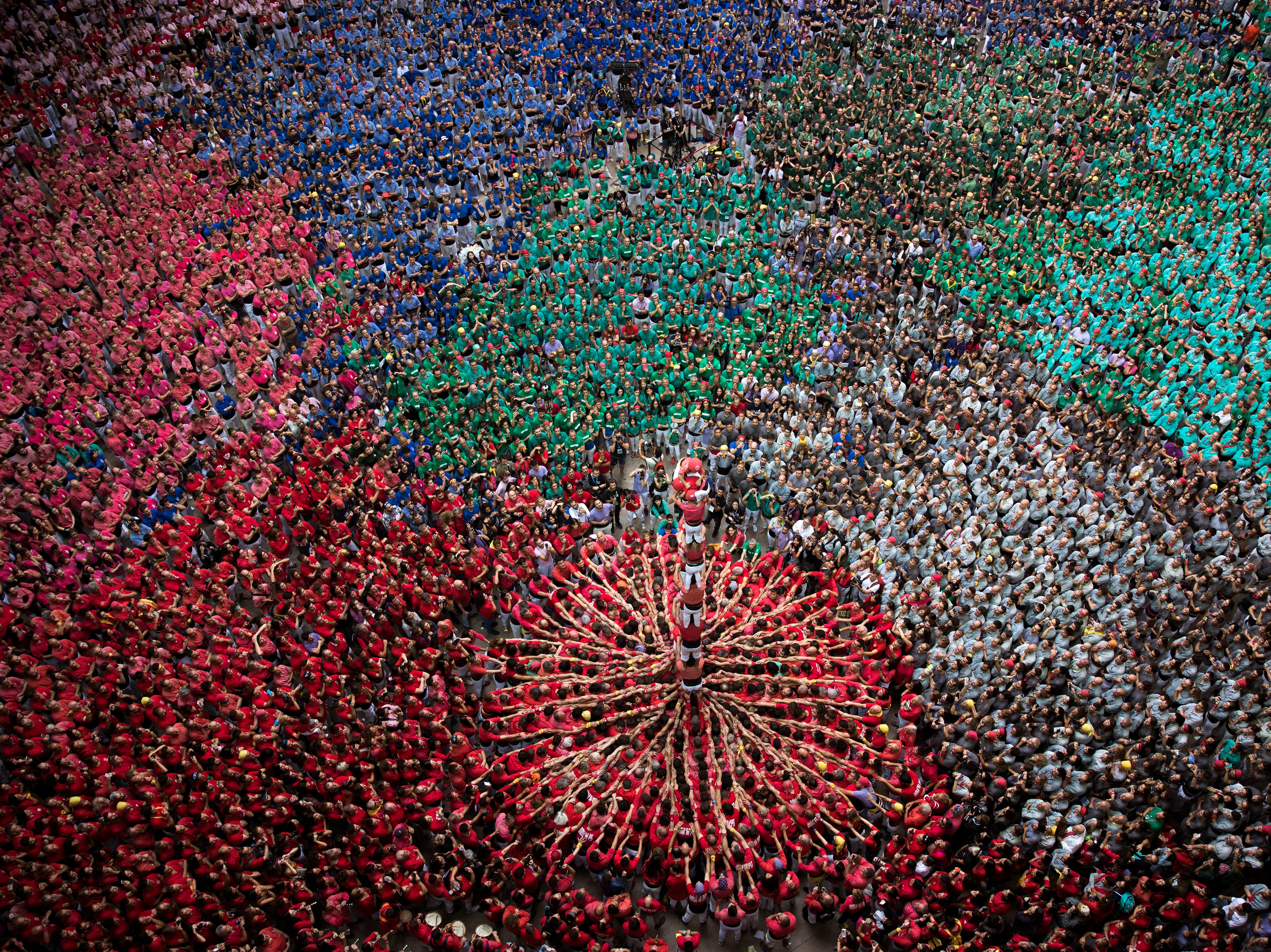 """Members of the """"Colla Joves Xiquets de Valls"""" complete their human tower during the 27th Human Tower Competition in Tarragona, Spain, on Oct. 7, 2018."""