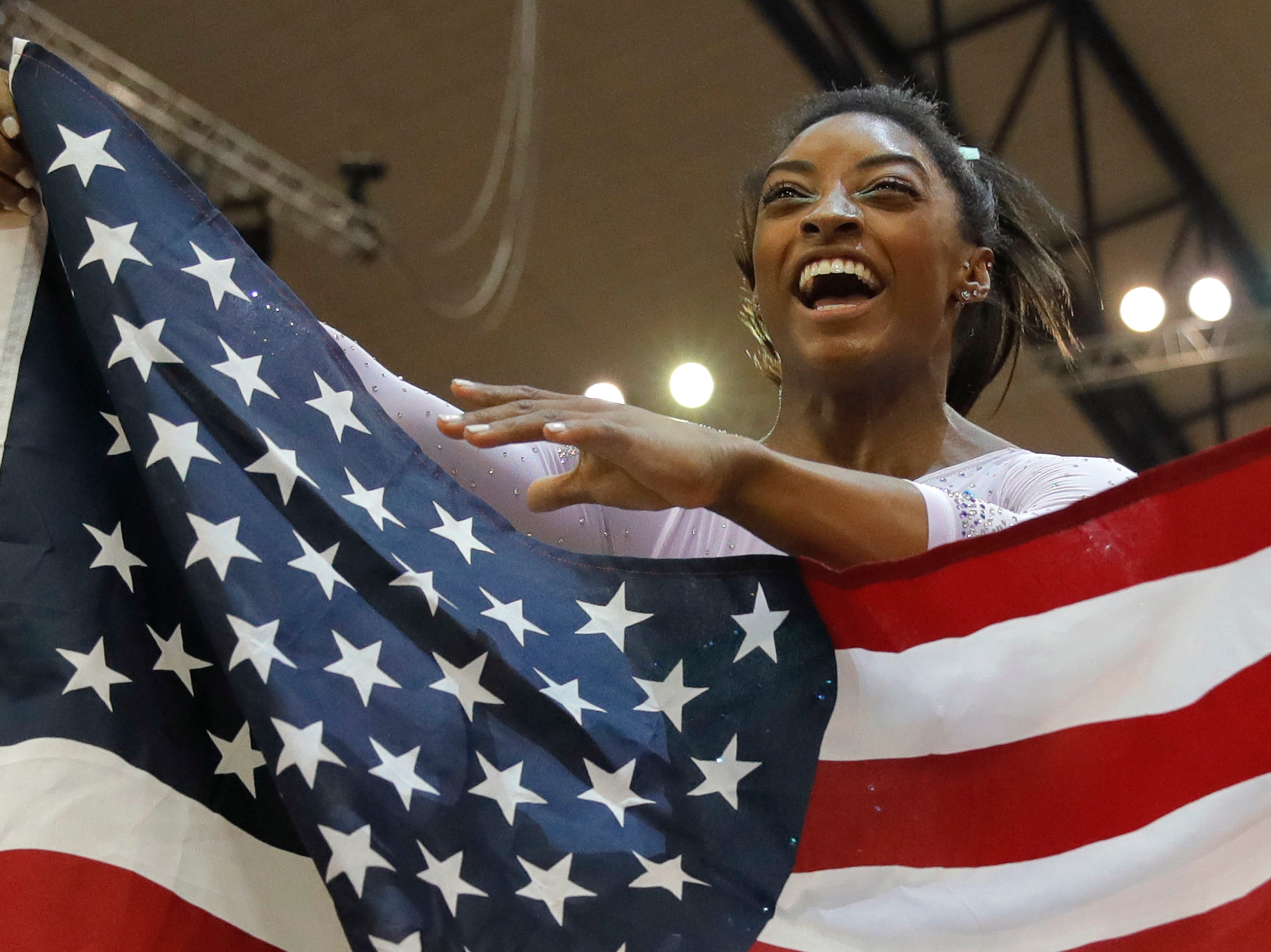 Gold medallist and four-times All-Around world champion Simone Biles of the U.S. celebrates with the national flag after the Women's All-Around Final of the Gymnastics World Chamionships at the Aspire Dome in Doha, Qatar, Nov. 1, 2018.