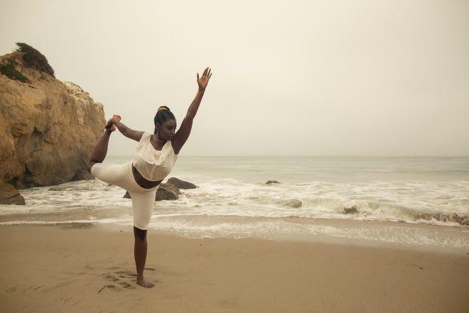 Shaina Lynn holds a yoga pose on the beach.