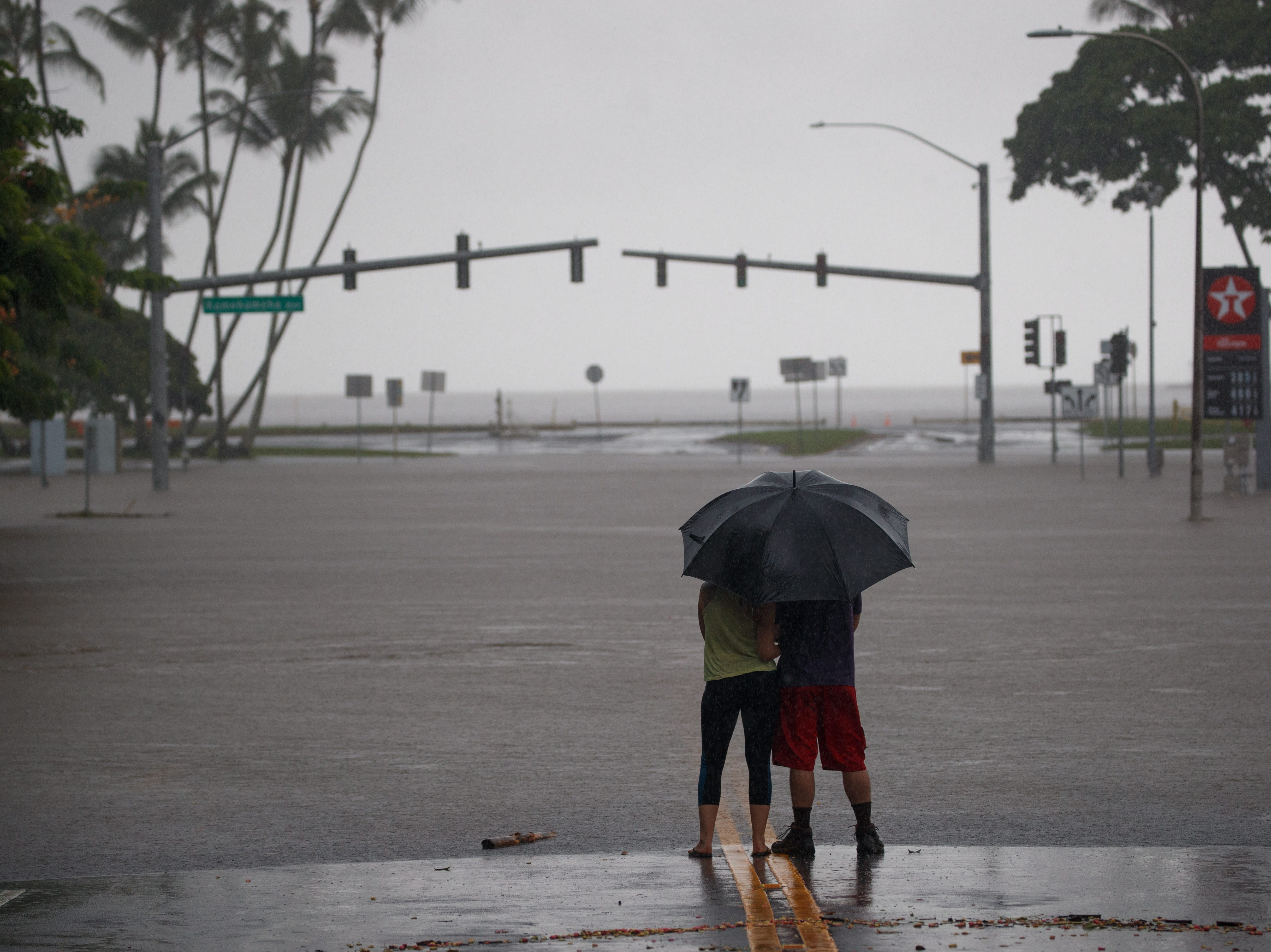 Aug. 24, 2018: Michelle Montgomery (L) and Eric Leifer (R) share a moment under an umbrella, as they view the flooded Pauahi St and Kamehameha Ave intersection in Hilo, Hawaii.  Torrential rains from Hurricane Lane inundated the eastern half of the island of Hawaii, causing disruptions for residents and visitors alike.