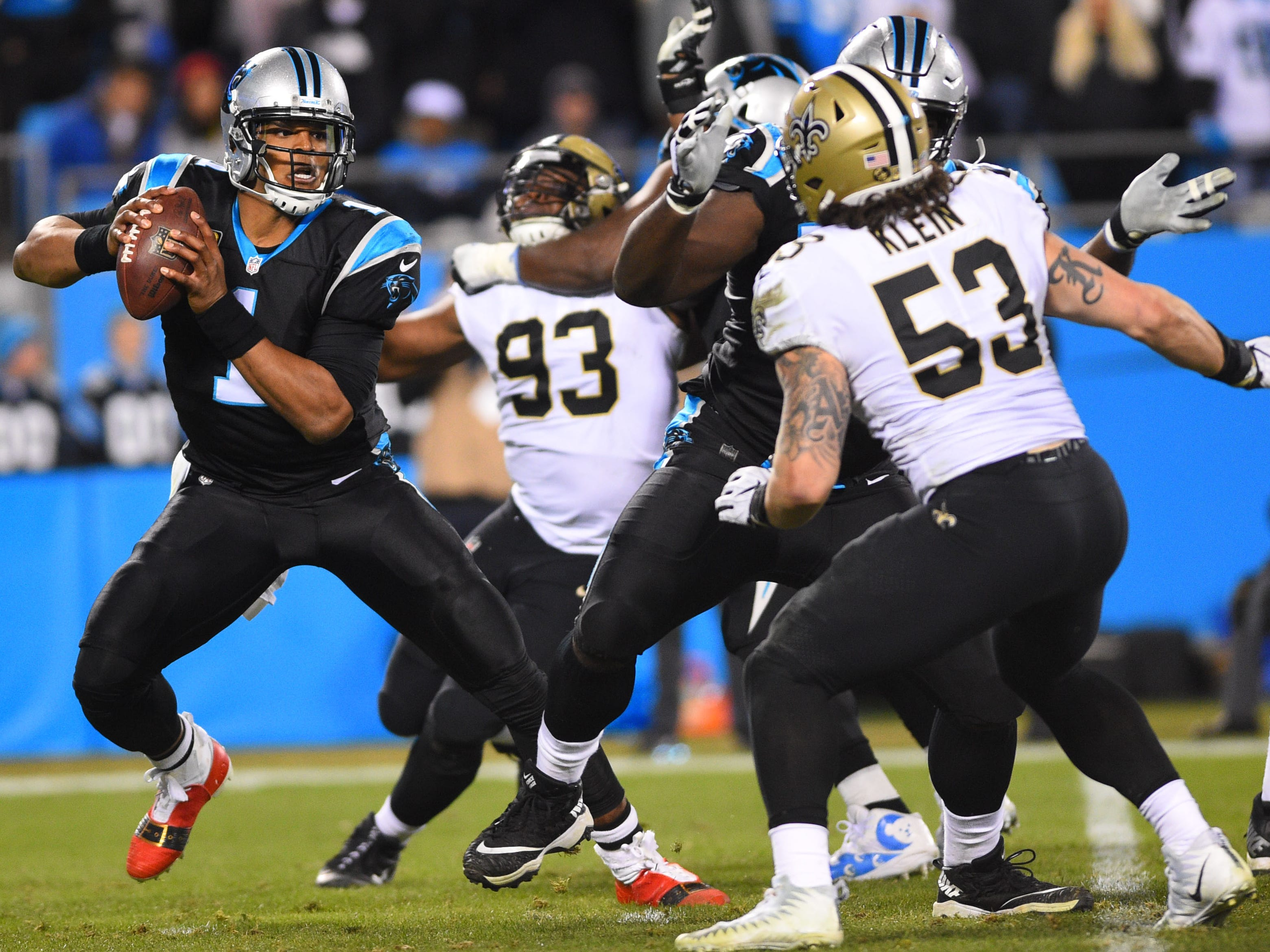 Carolina Panthers quarterback Cam Newton looks to pass as New Orleans Saints defensive tackle David Onyemata (93) and outside linebacker A.J. Klein (53) pressure in the second quarter at Bank of America Stadium.