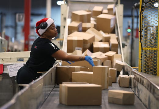 U.S. Postal Service mail handler Nikeisha Mitchell sorts packages at the U.S. Postal service's Royal Palm