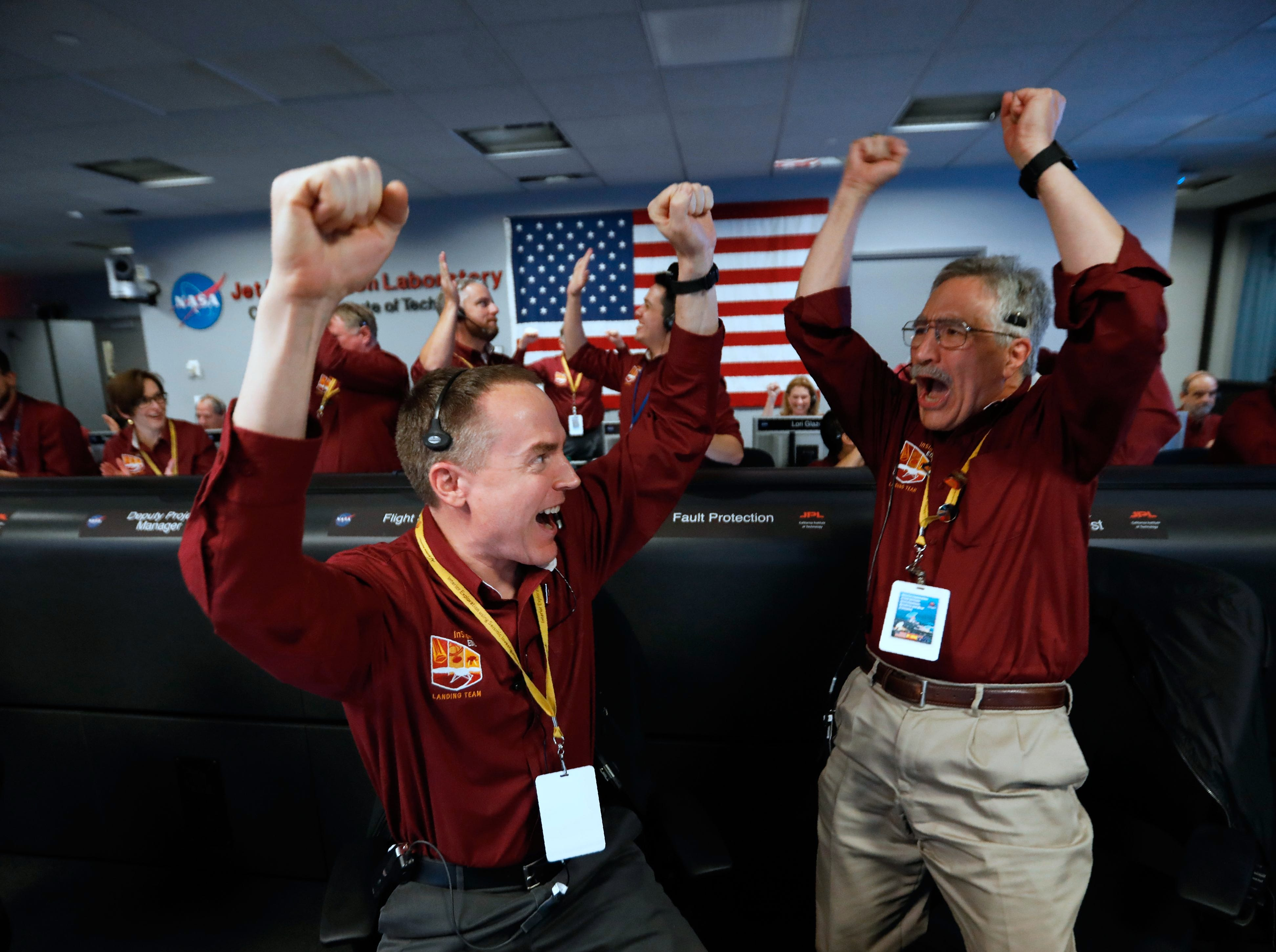 NASA engineers on the flight team, Kris Bruvold (L) and Sandy Krasner (R) celebrate the InSight spacecraft's successfull landing on the planet Mars from the Mission Support area in the Space Flight Operations facility at the NASA Jet Propulsion Laboratory (JPL) in Pasadena, California on Nov. 26, 2018. Cheers and applause erupted at NASA's Jet Propulsion Laboratory as a $993 million unmanned lander, called InSight, touched down on the Red Planet and managed to send back its first picture.