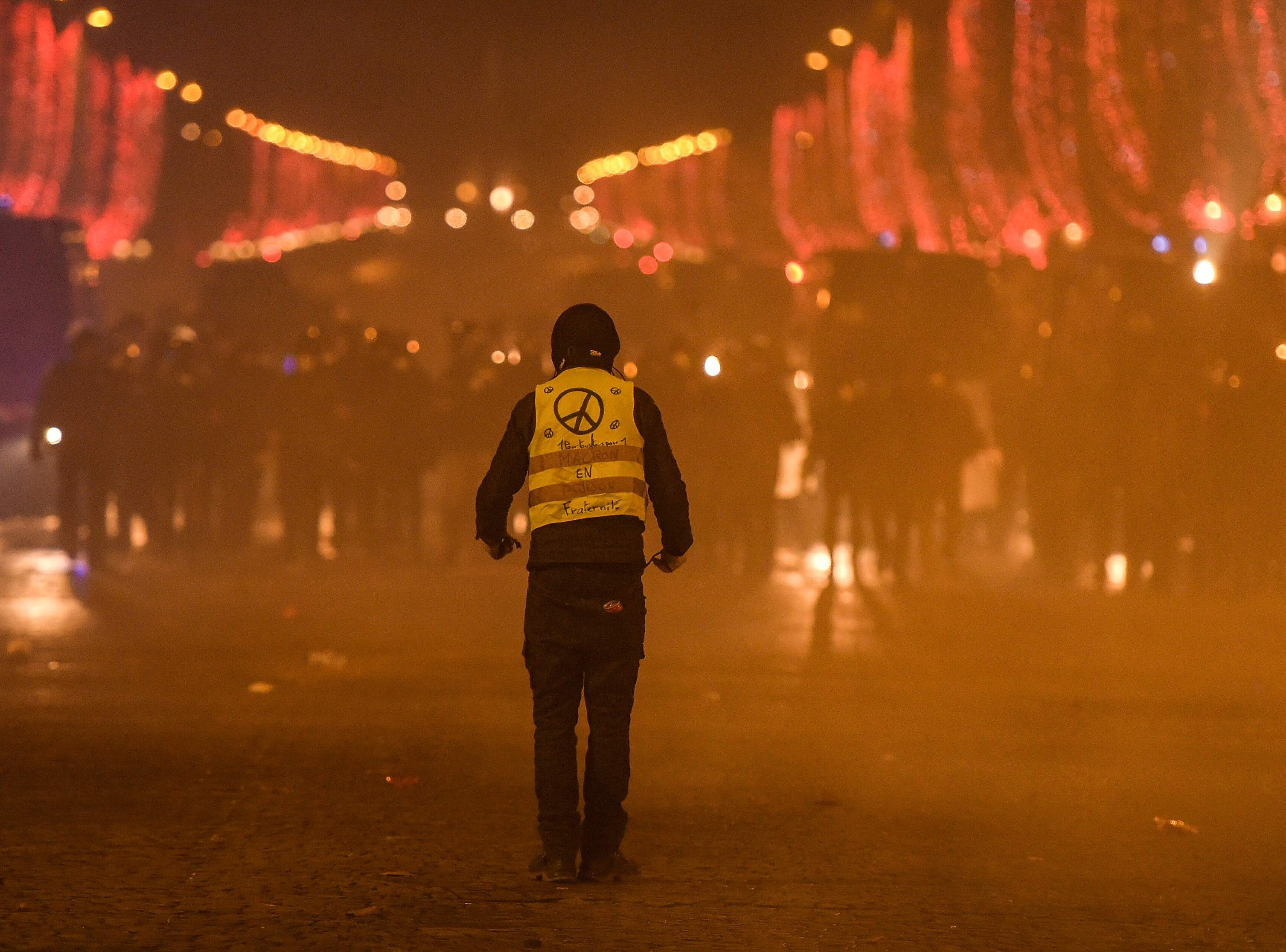 A protester faces riot police during a demonstration of the 'Yellow Vests' (Gilets Jaunes) against rising costs of living on the Champs Elysees avenue in Paris on Dec. 8, 2018.