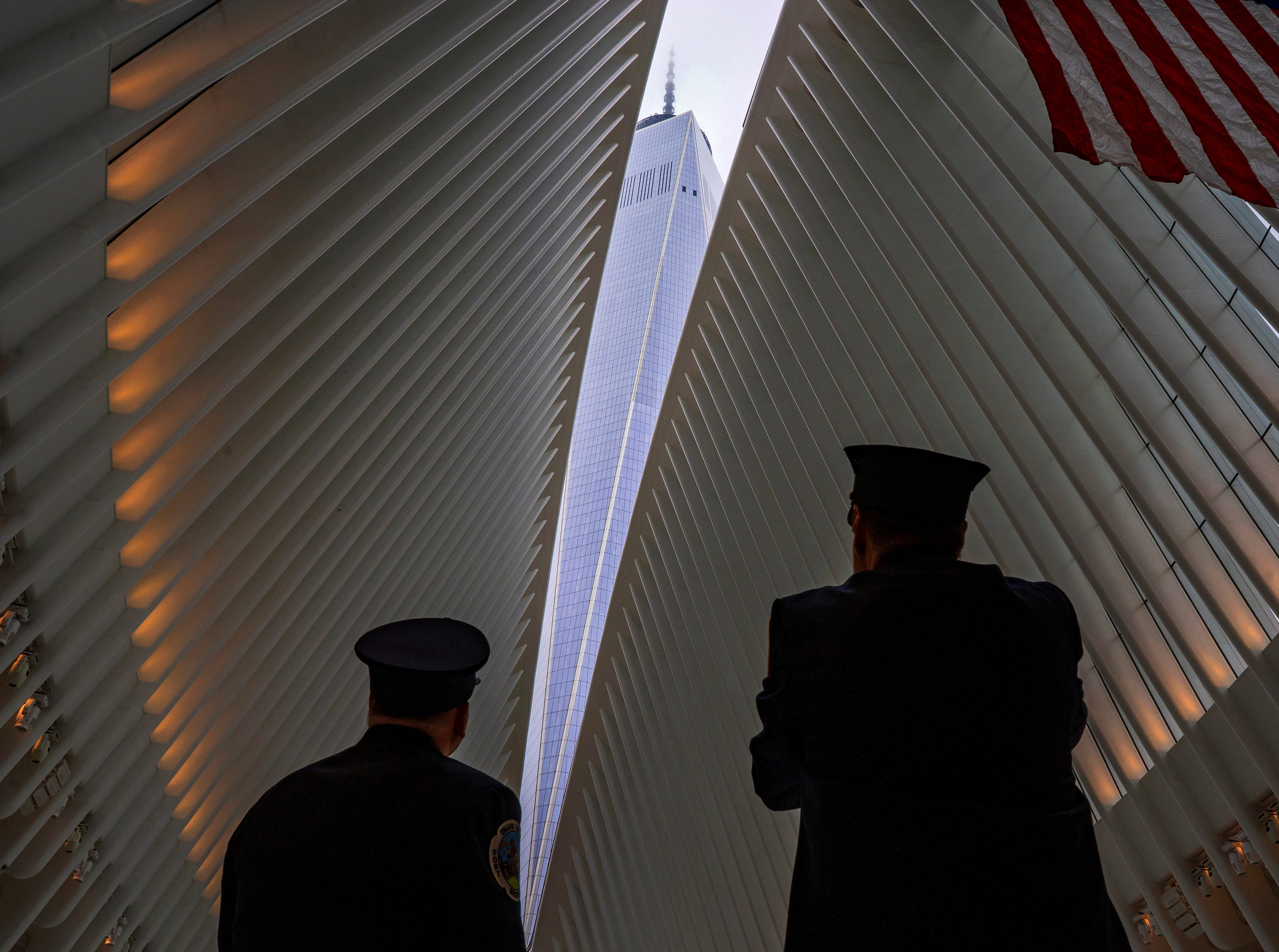 Sept. 11, 2018: Two members of the New York City fire department look towards One World Trade Center through the open ceiling of the Oculus, part of the World Trade Center transportation hub in New York on the anniversary of 9/11 terrorist attacks. The transit hall ceiling window was opened just before 10:28 a.m., marking the moment that the North Tower of the World Trade Center collapsed on Sept. 11, 2001.