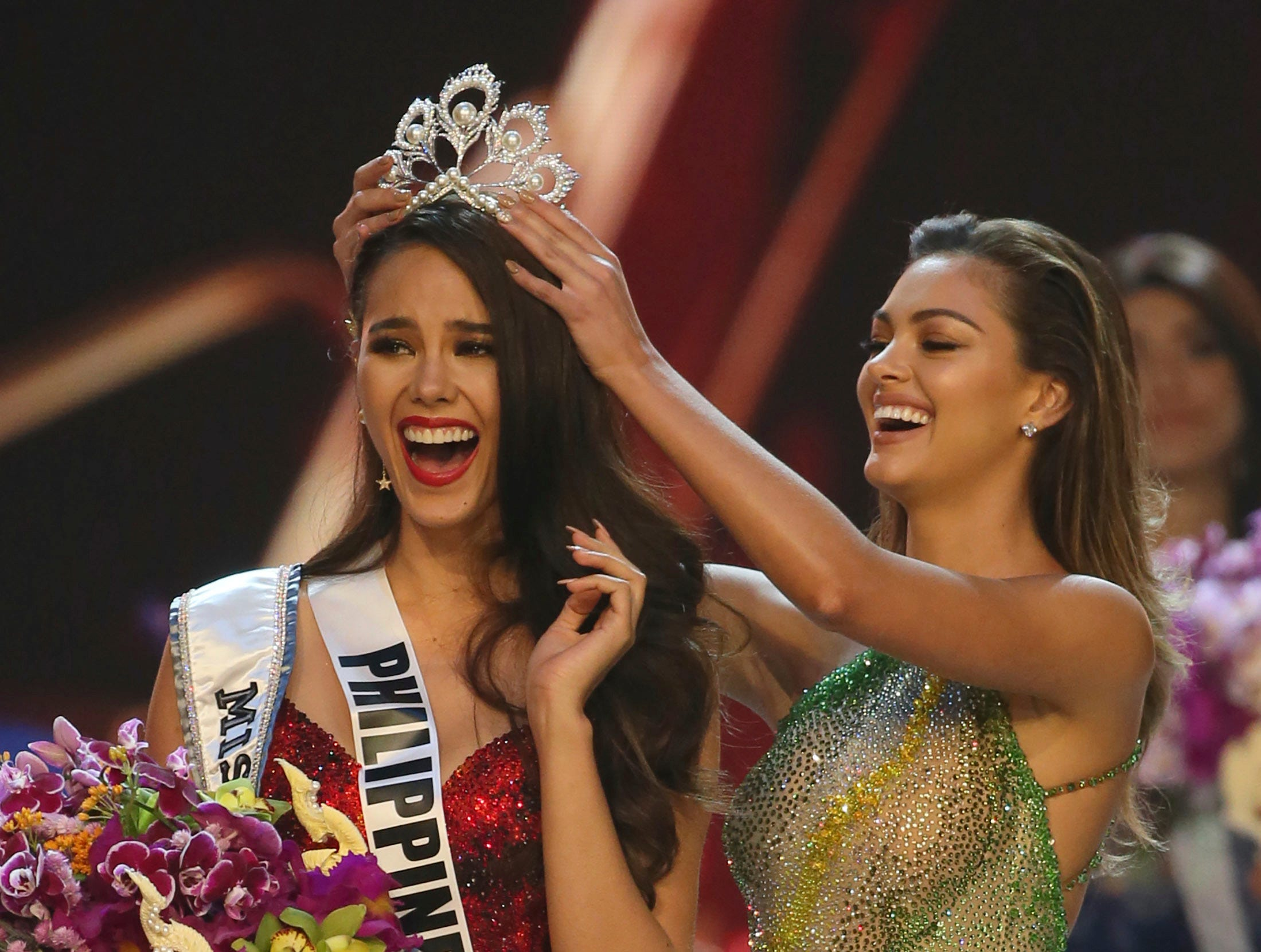 Catriona Gray of the Philippines, left, reacts as she is crowned the new Miss Universe 2018 by Miss Universe 2017 Demi-Leigh Nel-Peters during the final round of the 67th Miss Universe competition in Bangkok, Thailand, Monday, Dec. 17, 2018.(AP Photo/Gemunu Amarasinghe) ORG XMIT: XVT132