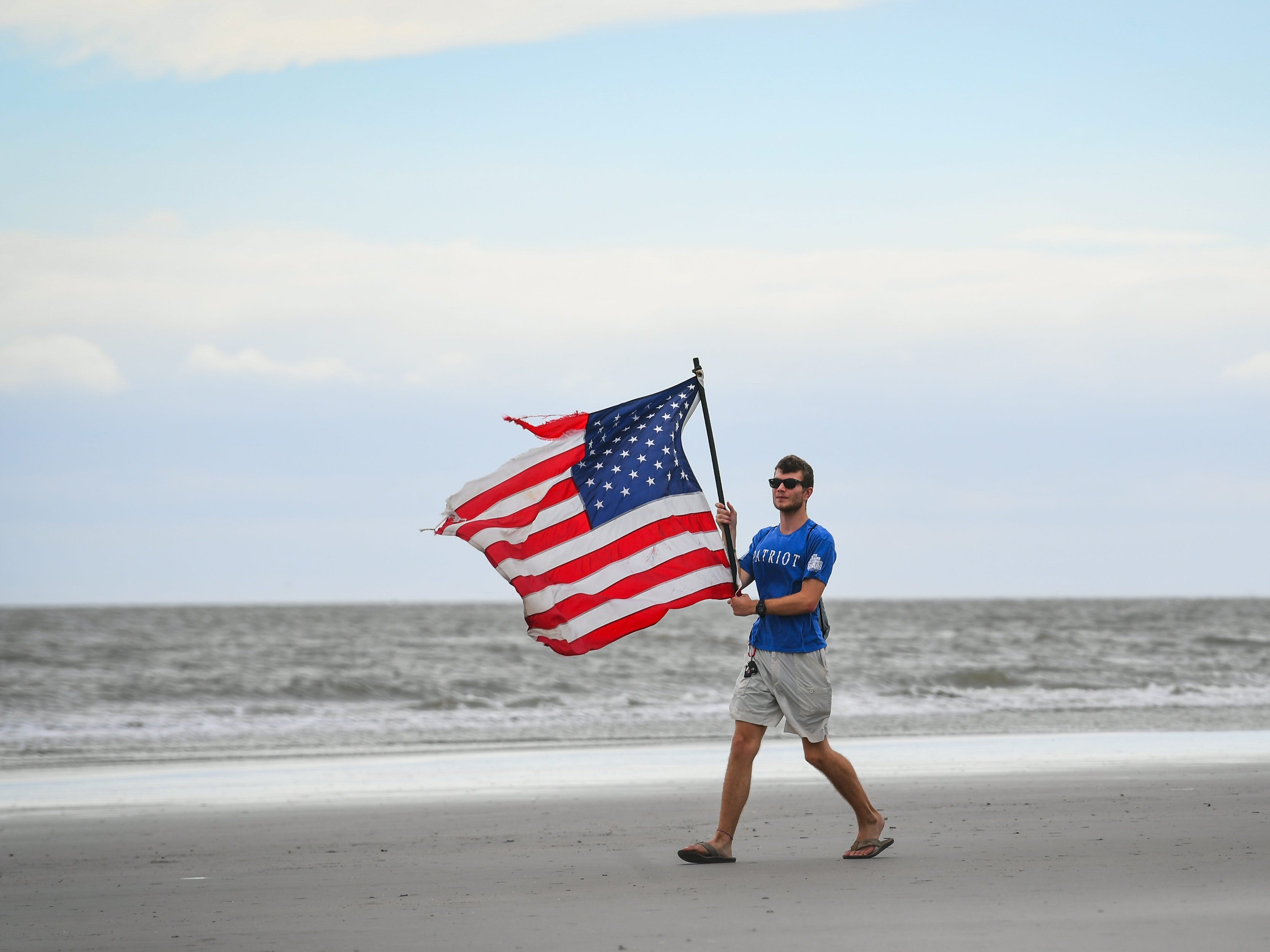 Sept. 14, 2018: Mason Moise, 18, from Charleston, S.C., carries a U.S. flag in the increasing winds on Isle of Palms, S.C. prior to the arrival of Hurricane Florence.