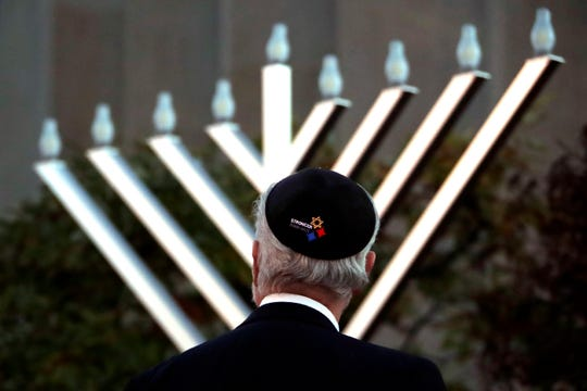 Rabbi Jeffrey Myers watches the installation of a menorah outside the Tree of Life Synagogue before holding a celebration on the first night of Hanukkah, Sunday, Dec. 2, 2018, in the Squirrel Hill neighborhood of Pittsburgh. A gunman shot and killed 11 people while they worshipped Saturday, Oct. 27, at the temple. (AP Photo/Gene J. Puskar) ORG XMIT: PAGP101