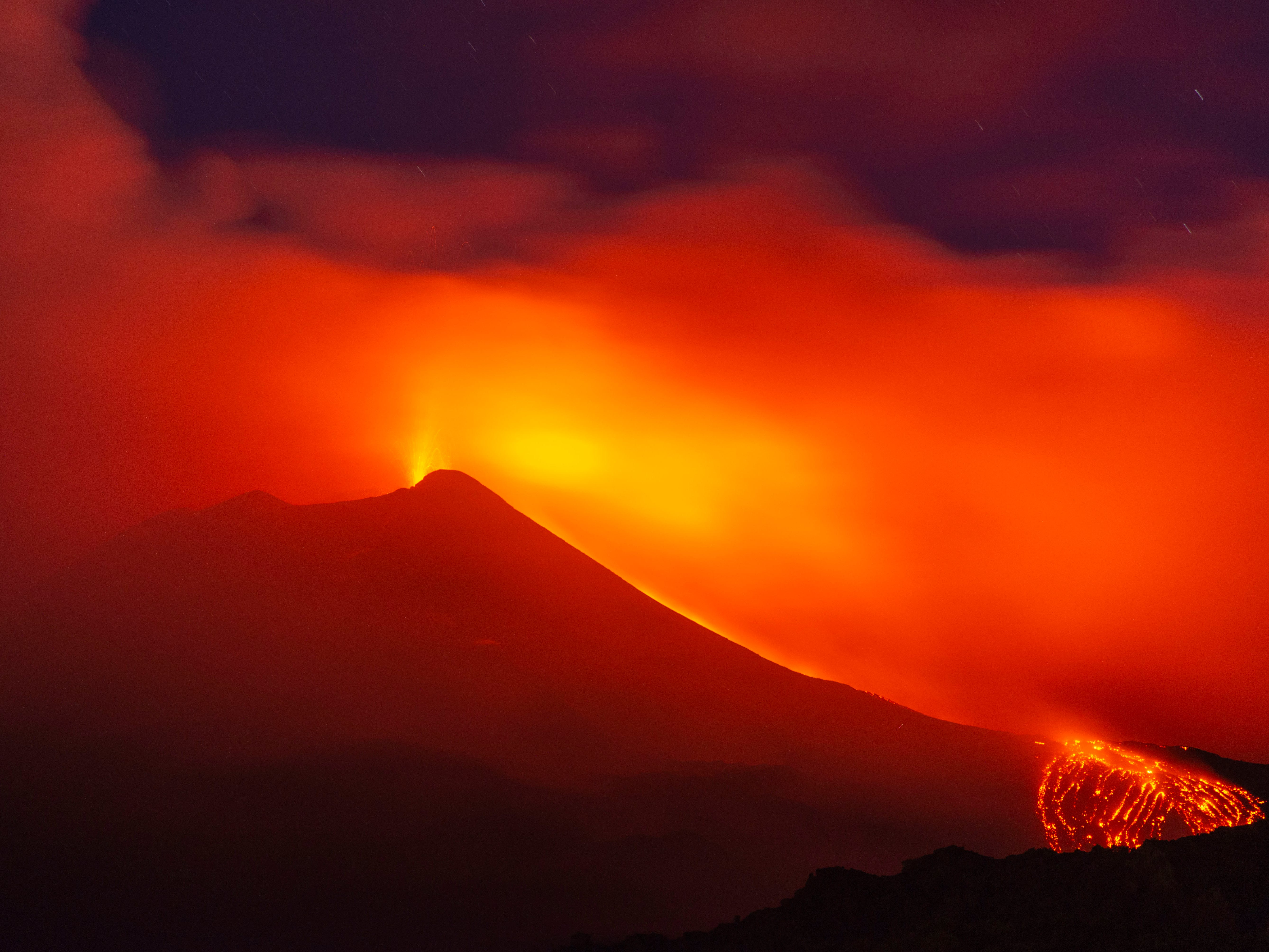 """Aug. 25, 2018: Mount Etna volcano spews lava during an eruption early.  Mount Etna in Sicily has roared back into spectacular volcanic action, sending up plumes of ash and spewing lava. Italy's National Institute of Geophysics and Vulcanology (INGV) says that the volcano, which initially """"re-awoke"""" in late July, sprang into fuller action  by shooting up chunks of flaming lava as high as 500 feet almost constantly."""