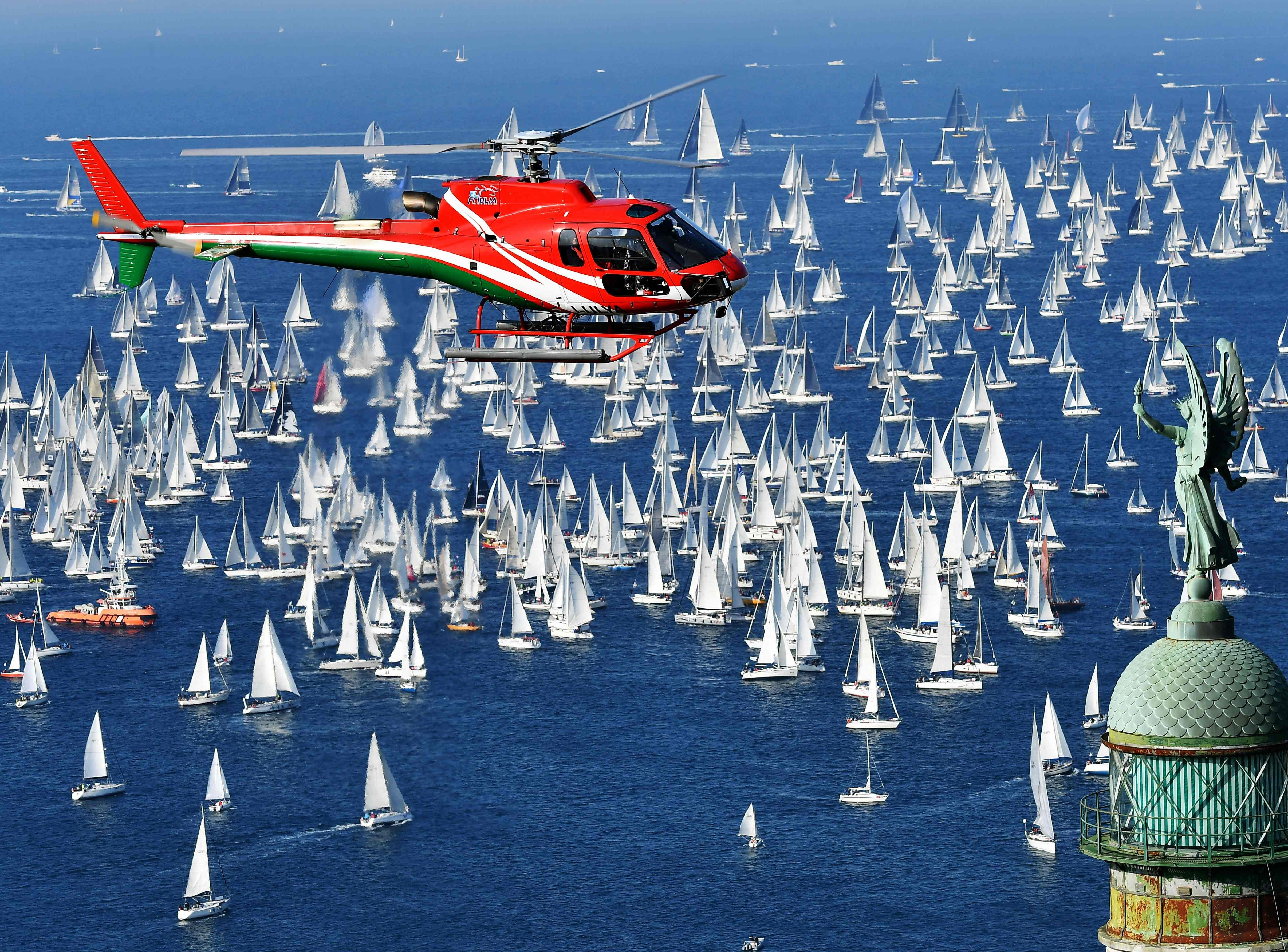 """Boats sail past the """"Victory Lighthouse"""" during the 50th Barcolana regatta in the Gulf of Trieste on Oct. 14, 2018. With some 2700 vessels, The Barcolana, has the most particpants of any sailing regatta in the world."""