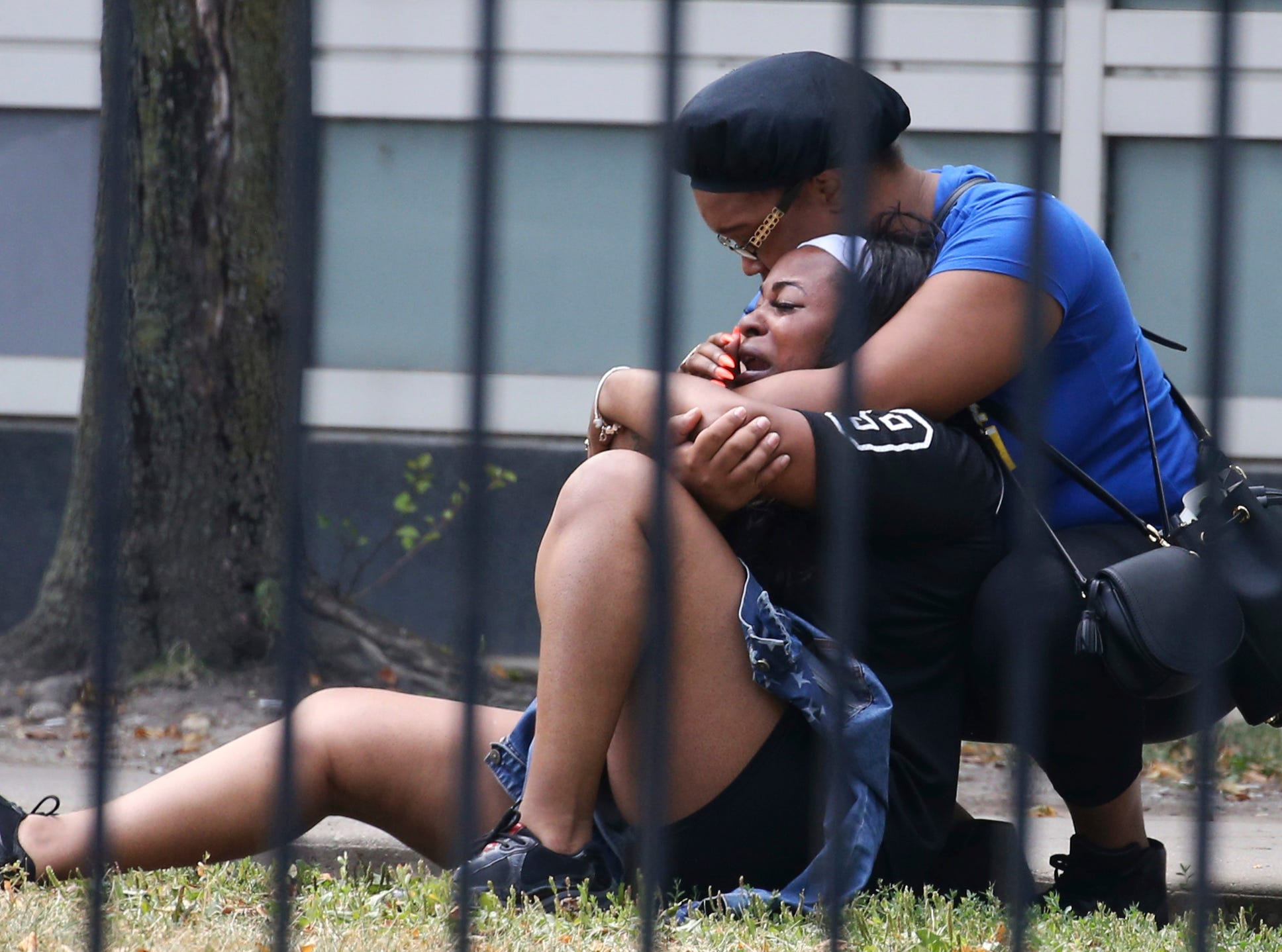 Aug. 5, 2018: Two women cry outside the Stroger Hospital in Chicago after they were asked to leave due to overwhelming crowds of family and friends of shooting victims.