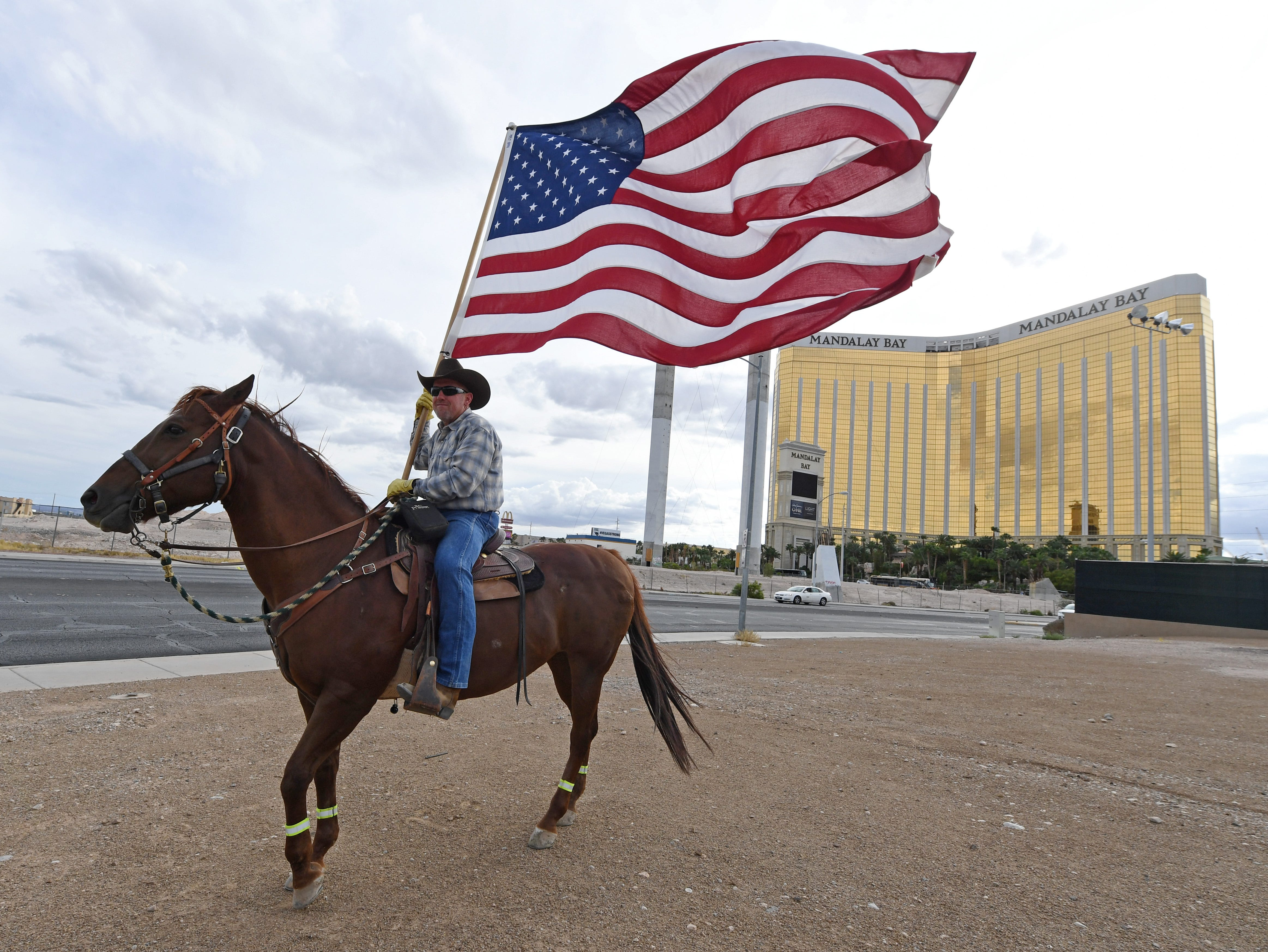 Rafael Sarabia of Nevada holds an American flag as he rides his horse Red Sonja outside the Las Vegas Village across from Mandalay Bay Resort and Casino as a tribute to those killed in last year's massacre at the site on Oct. 1, 2018 in Las Vegas, Nev. On October 1, 2017, Stephen Paddock opened fire from the 32nd floor of Mandalay Bay on the Route 91 Harvest country music festival in Las Vegas killing 58 people and injuring more than 800 in the deadliest mass shooting event in U.S. history.