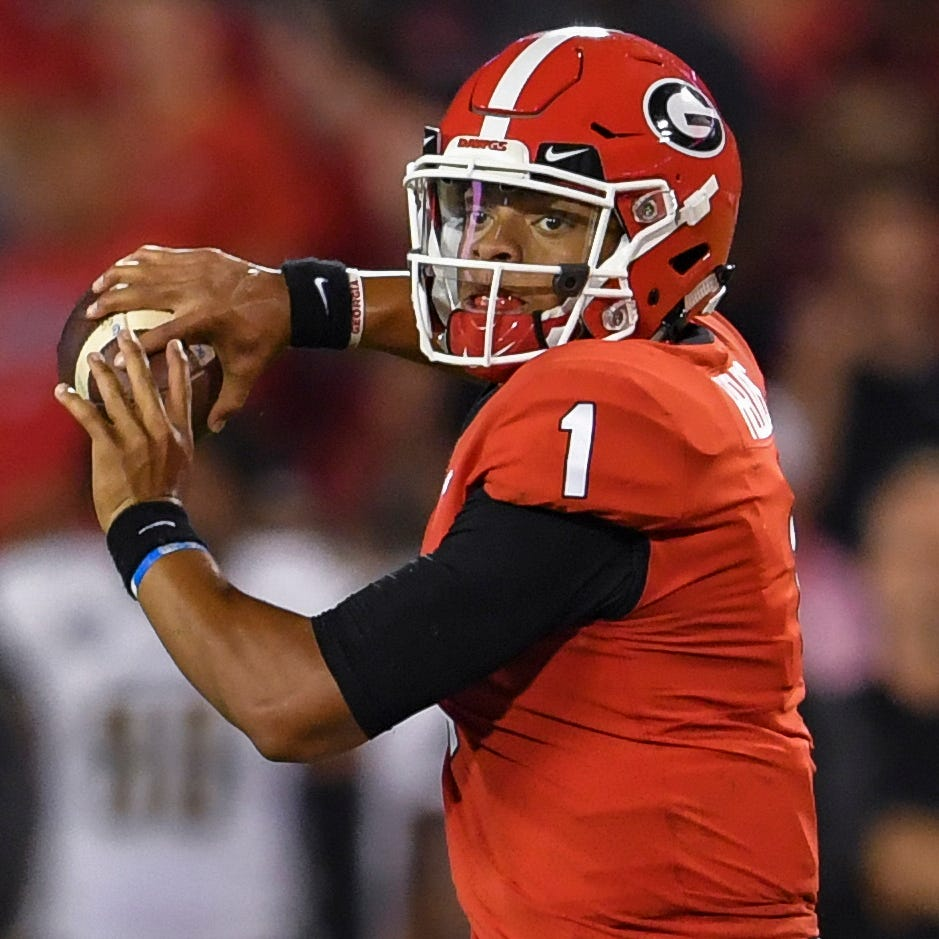 Justin Fields looks to pass the ball downfield...