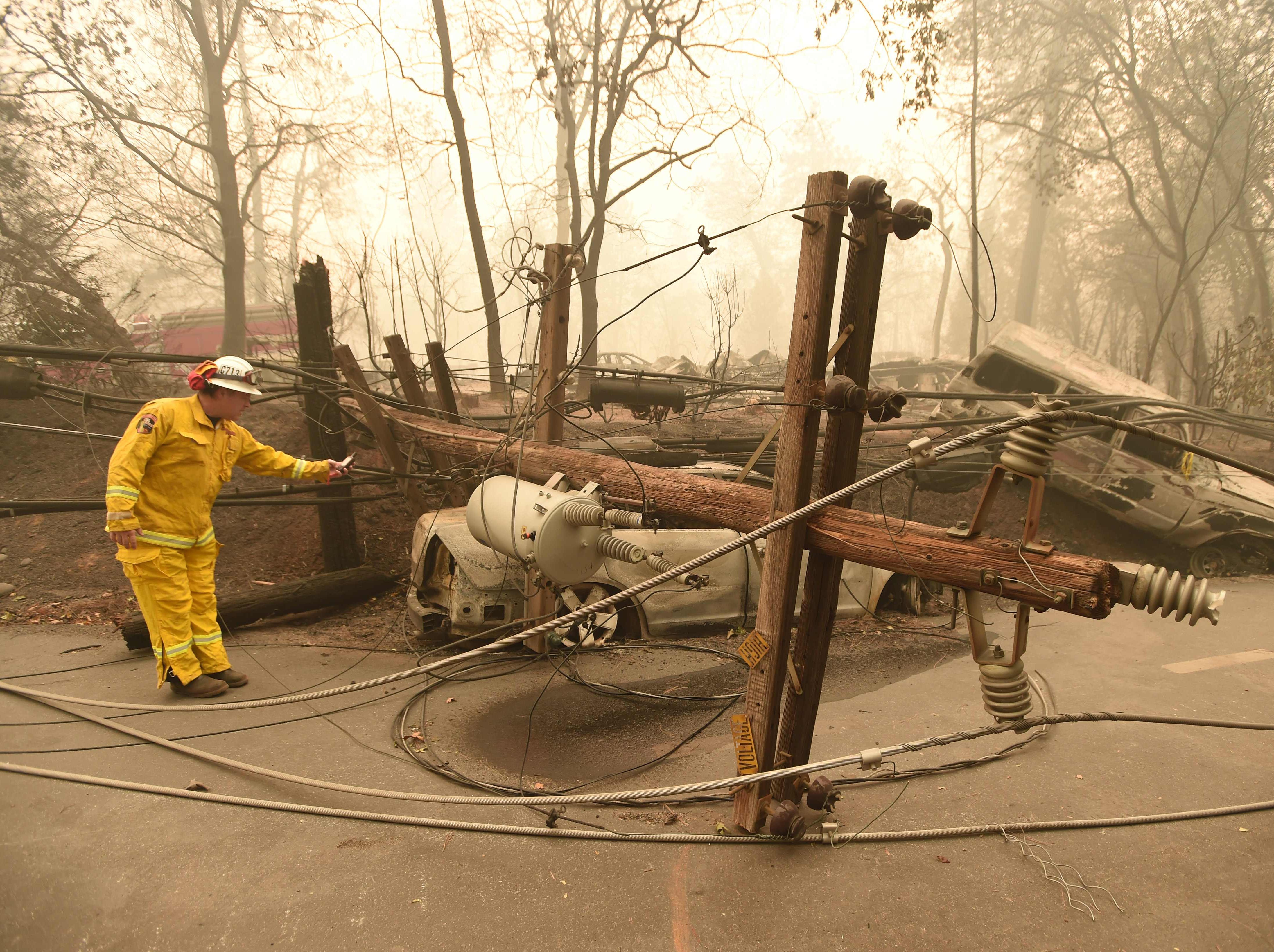 CalFire firefighter Scott Wit surveys burned out vehicles near a fallen power line on the side of the road after the Camp fire tore through the area in Paradise, Calif. on November 10, 2018.