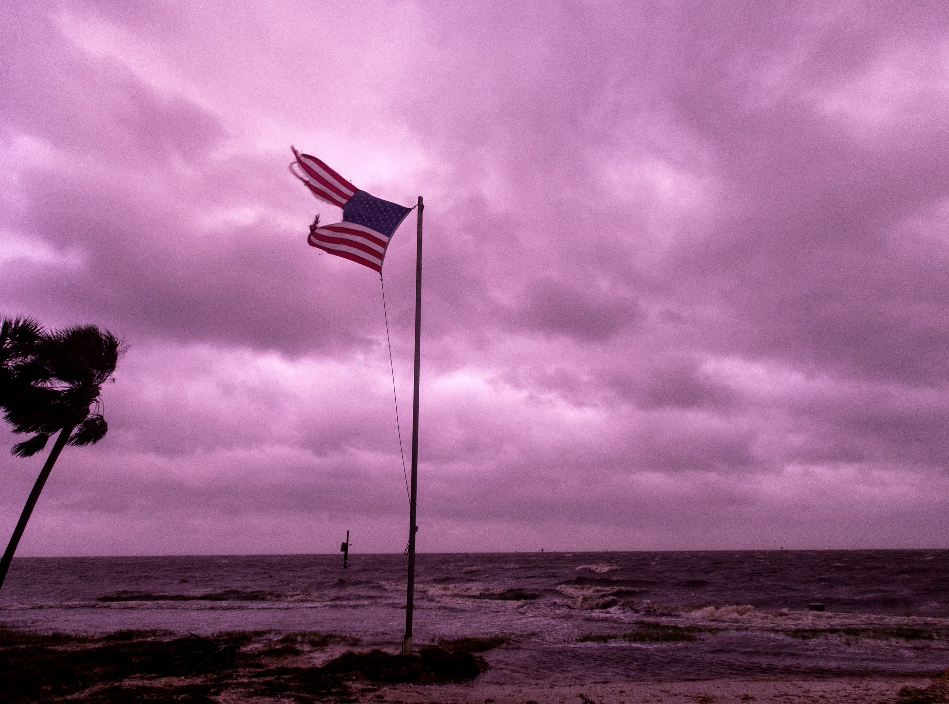 An American flag battered by Hurricane Michael continues to fly in the in the rose colored light of sunset at Shell Point Beach on Oct. 10, 2018 in Crawfordville, Fla.The hurricane hit the Florida Panhandle as a category 4 storm.