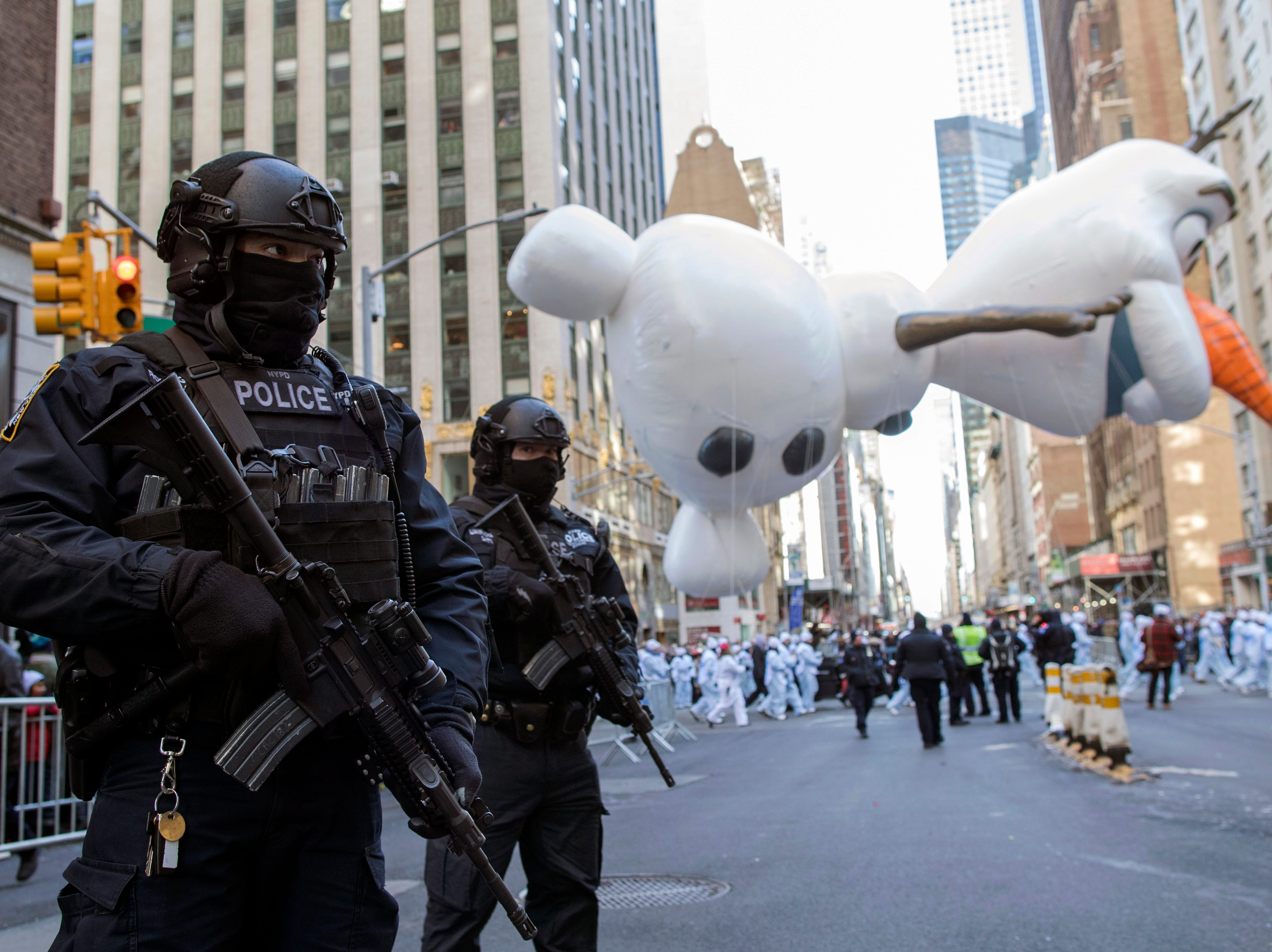 Heavily-armed police officers stand guard as the Olaf balloon floats down 6th Avenue during the 92nd annual Macy's Thanksgiving Day Parade, Nov. 22, 2018, in New York.