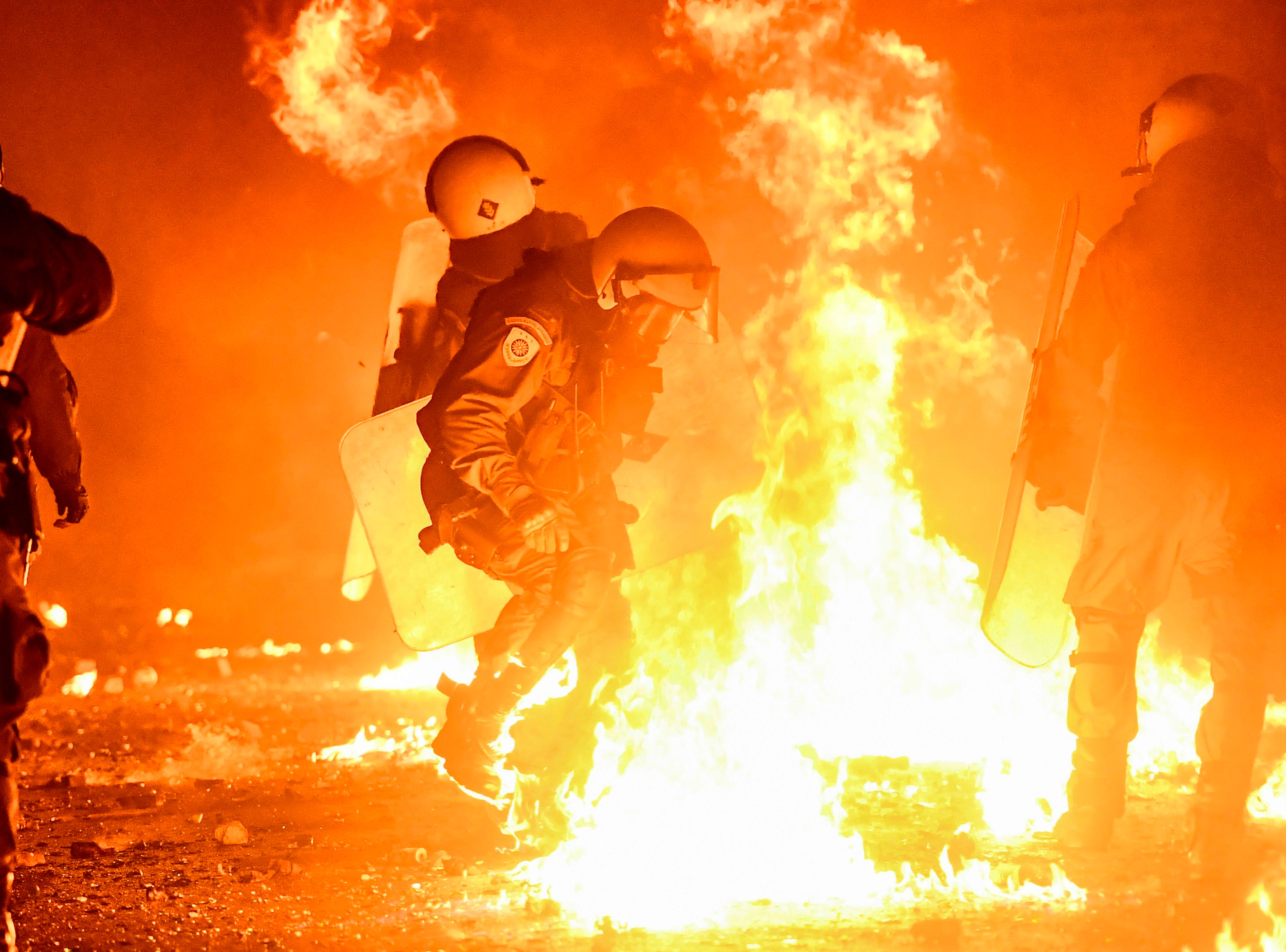 Flames from petrol bombs burn after exploding close to anti-riot police officers during a demonstration in downtown Athens on Dec. 6, 2018 to commemorate the 10th anniversary of the fatal shooting of a teenager which sparked major riots in Greece in 2008.