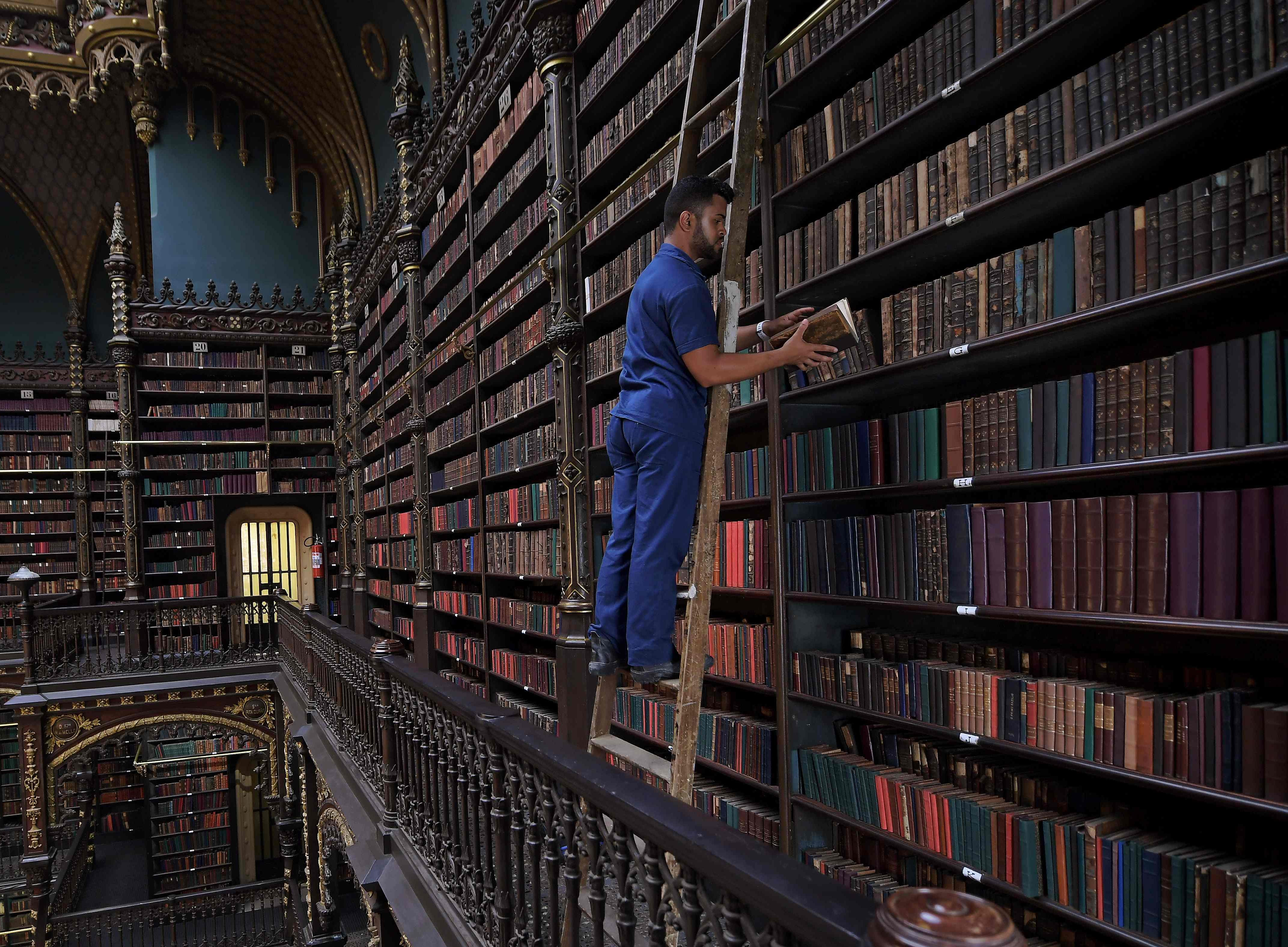 Employee Jeferson Deodata da Silva selects a book from the shelves of the Royal Portuguese Cabinet of Reading in Rio de Janeiro, Brazil, on Nov. 19, 2018. The institution was founded in 1837 by a group of forty-three Portuguese immigrants -political refugees- to promote culture among the Portuguese community in Brazil.