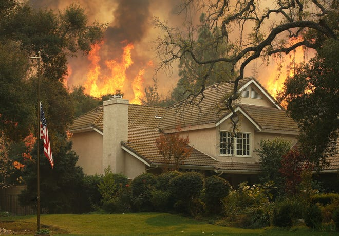 A U.S. flag is displayed at half-mast to honor shooting victims as the Woolsey Fire burns behind a home on Nov. 9, 2108, in Westlake Village next to Thousand Oaks, Calif. Twelve people were shot and killed on Nov. 7 at the Borderline Bar & Grill in Thousand Oaks.