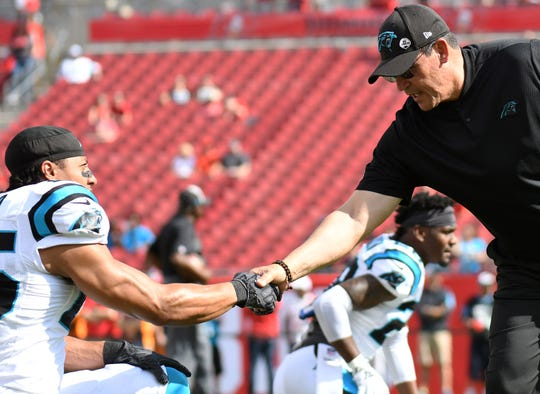 Panthers head coach Ron Rivera shakes hands with Eric Reid (25) prior to the game against the Tampa Bay Buccaneers at Raymond James Stadium on Dec. 2.