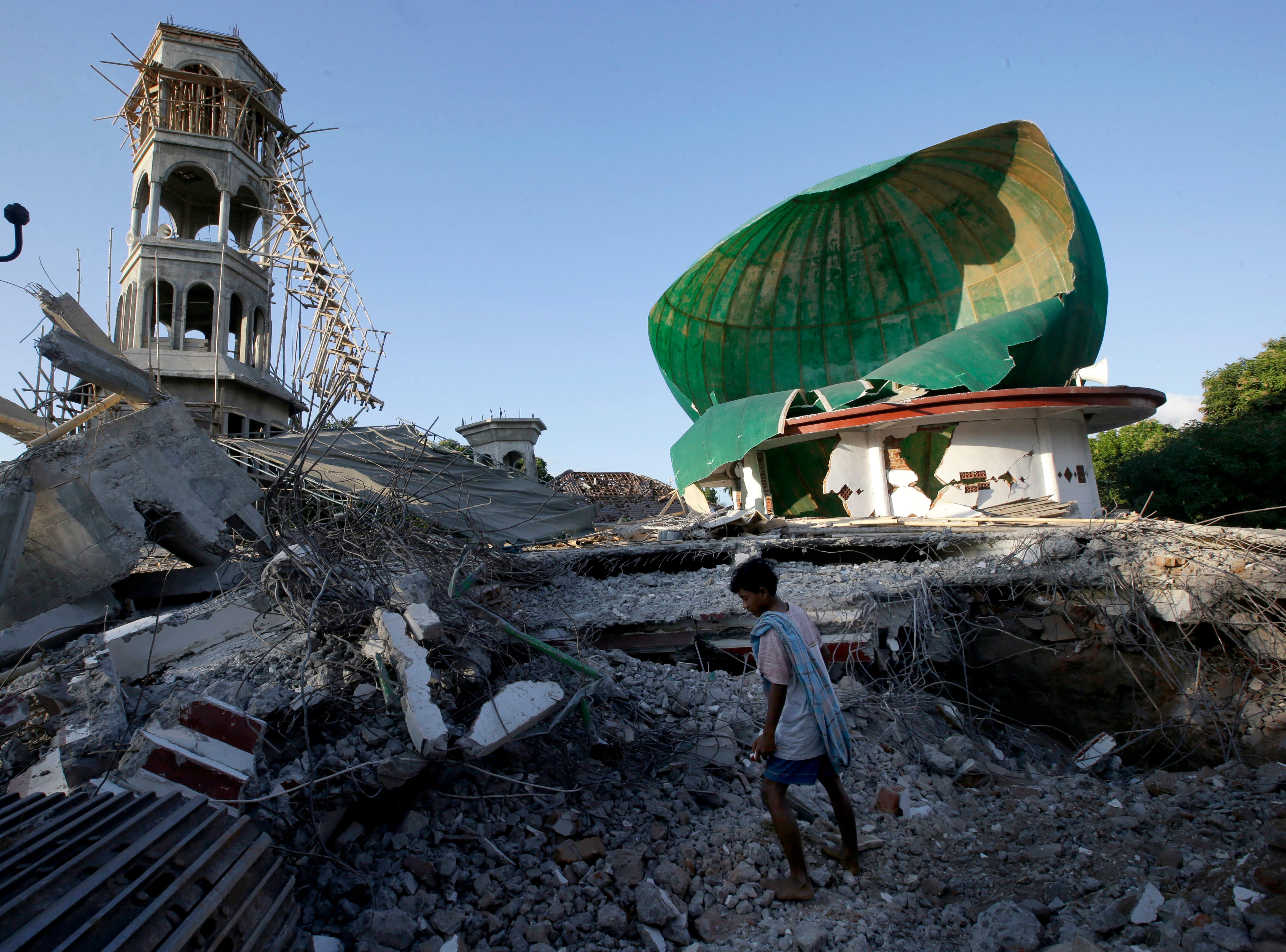 Aug. 7, 2018: A resident inspects a mosque damaged by an earthquake in North Lombok, Indonesia. The earthquakes that struck Lombok in eastern Indonesia in August, the biggest with a magnitude of 6.9, did not generate a tsunami but nonetheless caused widespread damage on the island and on nearby Bali, killing more than 500 people. Damages are estimated at more than $500 million.